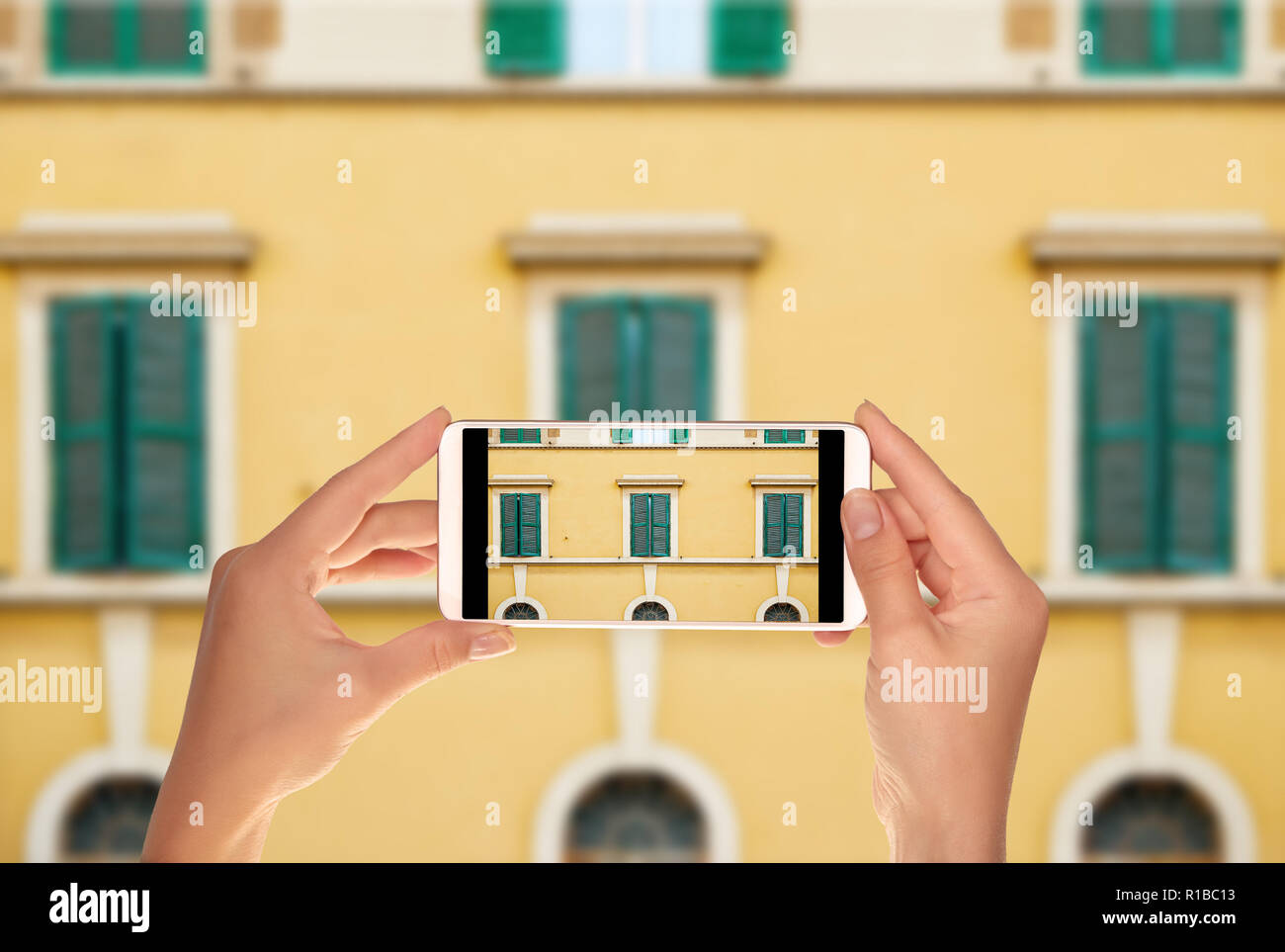 A tourist is taking a photo of pattern from windows of the facade of one of the buildings in Rome, Italy on a mobile phone - Stock Image