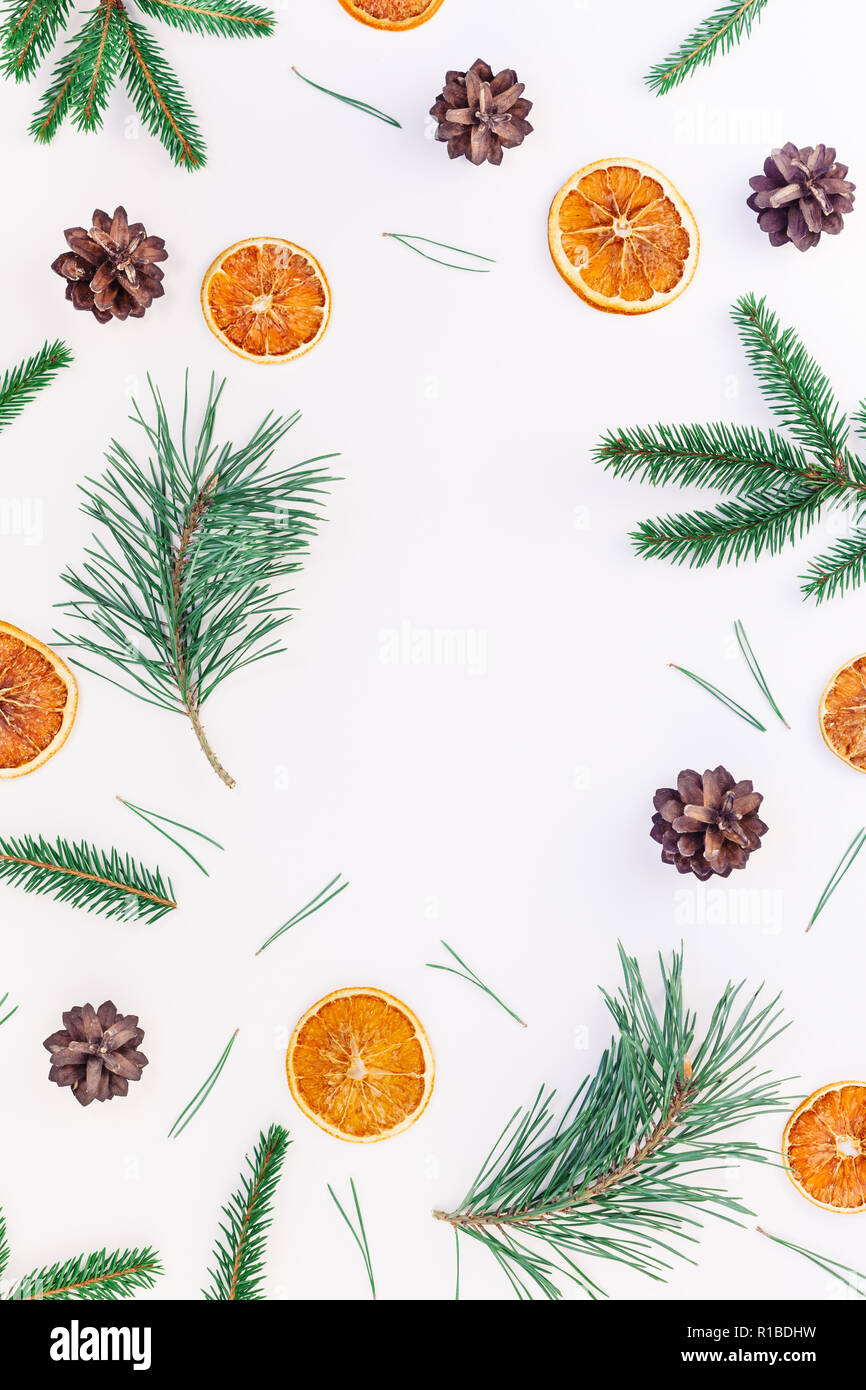 New Year Christmas pattern flat lay top view Xmas holiday handmade handicraft texture with fir tree pine branches cones dried oranges white background - Stock Image