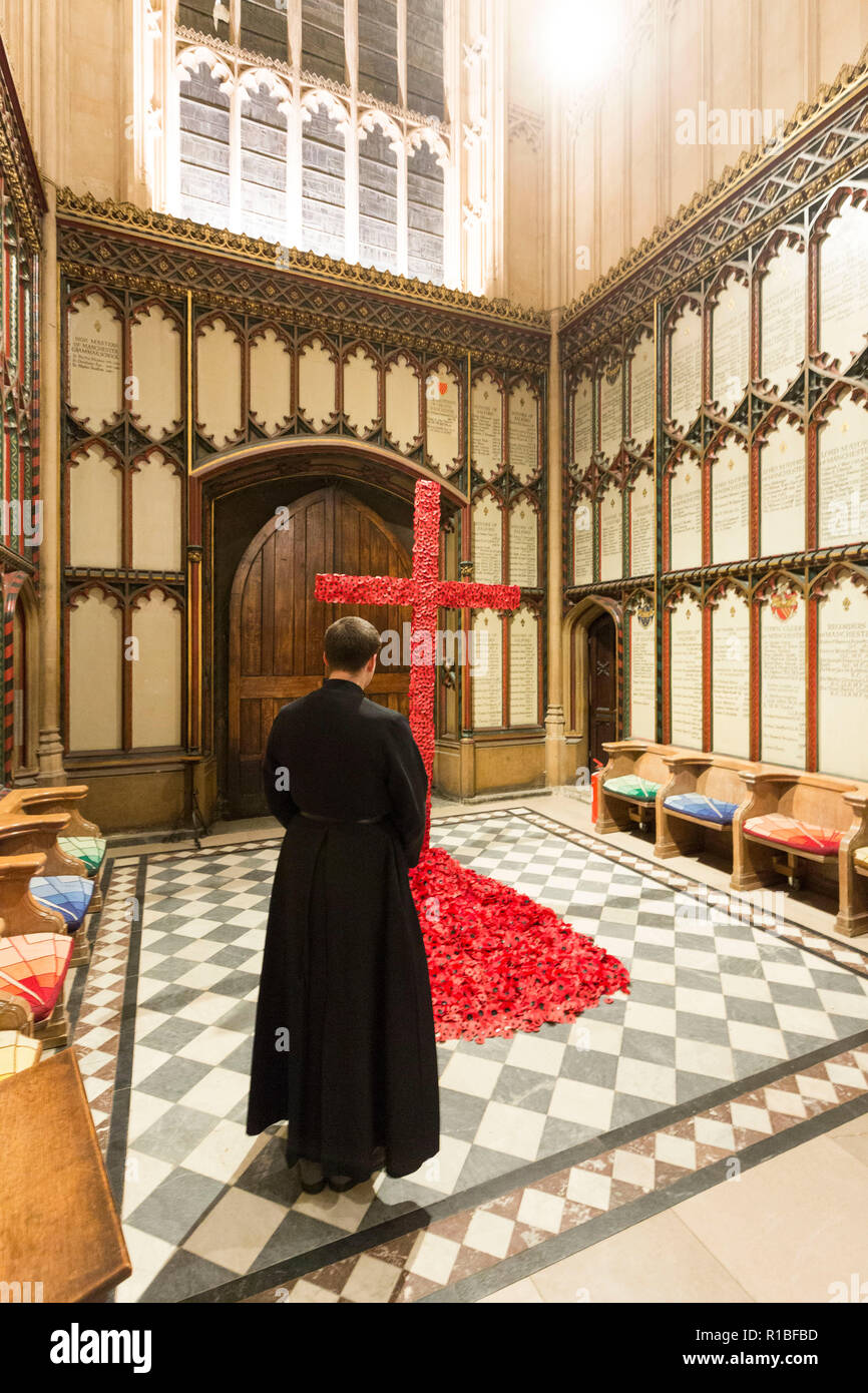 Manchester , England , 11th November 2018  Armistice Day in Manchester. Today (Sunday 11 November) marks 100 years since the end of the First World War. Inside Manchester Cathedral Gareth Screeton ,senior verger, reflects while looking at a poppy cross made by Helen Banping ,head flower arranger. This follwed a lone piper playing the traditional Scottish lament, Battle O'er, outside Manchester Cathedral to herald the start of commemorations. Around 1,000 other pipers will join in across the UK and around the world. Credit: Chris Bull/Alamy Live News. - Stock Image