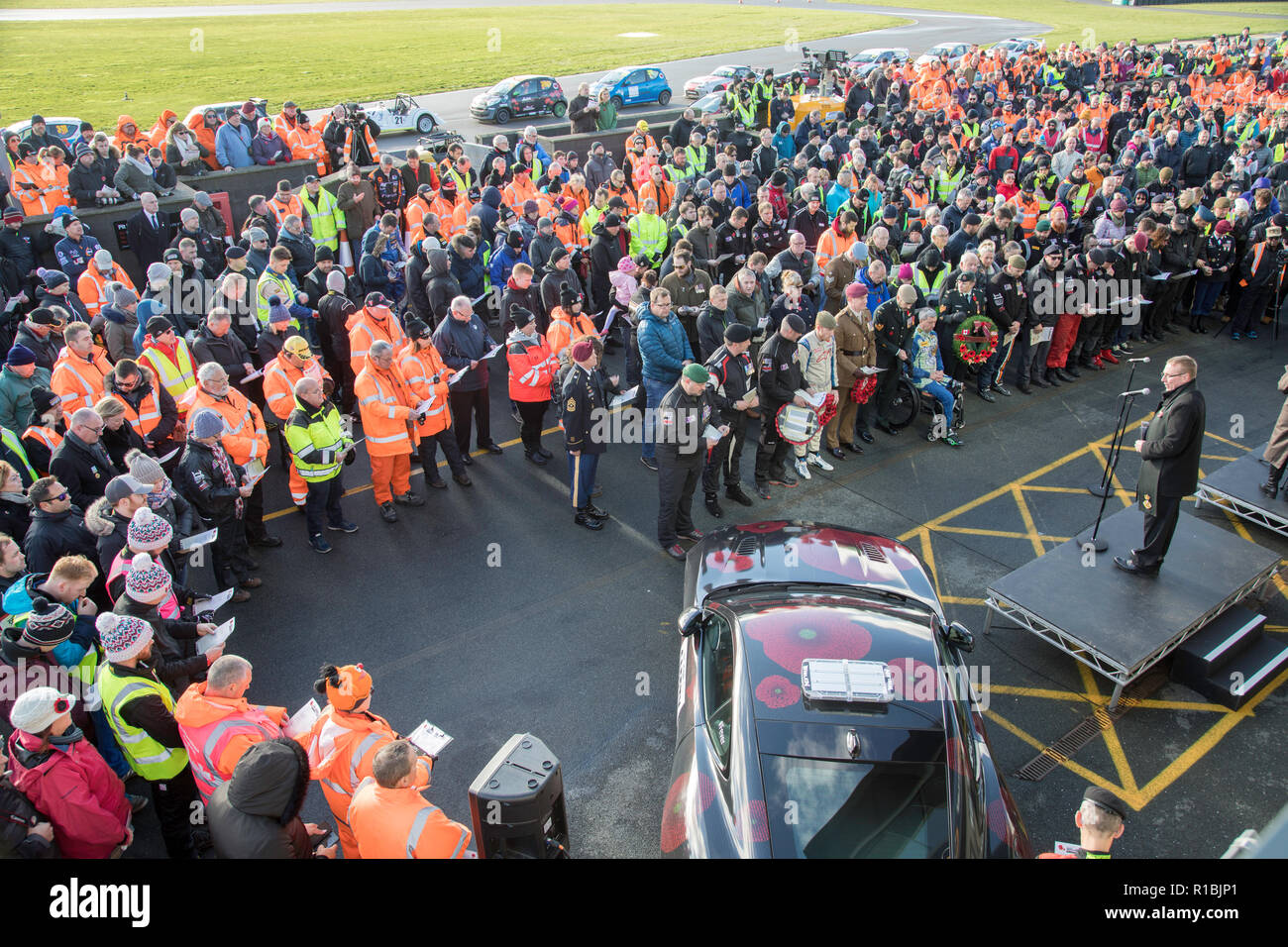 Ty Croes, Anglesey, Wales, UK. 11th Nov, 2018. Remembering the 100th anniversary of the end of WW1 at the 5th Race of Remembrance at the Anglesey Circuit in Wales. Mission Motorsport helpingthe current generation of veterans rehabilitate through motorsport. 50 teams of drivers come to race for 12 hours in a wide range of different cars. Racing is suspended on the 11th hour for a service of remembrance in the pit lane before returning to racing. The service includes a team of veterans from the US and Canadian armed forces Credit James Wadham / Alamy Live News - Stock Image