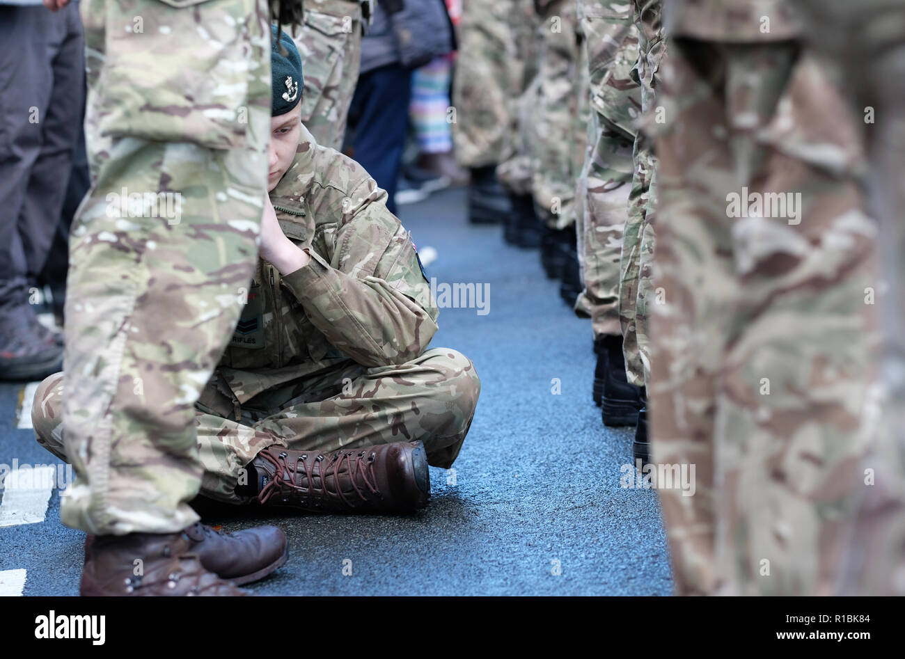 Hereford, Herefordshire, UK - Sunday 11th November 2018 - One young Combined Cadet Force ( CCF ) cadet rests among his colleagues after feeling unwell at the War Memorial during the Remembrance Sunday service in Hereford city centre.  Steven May / Alamy Live News - Stock Image