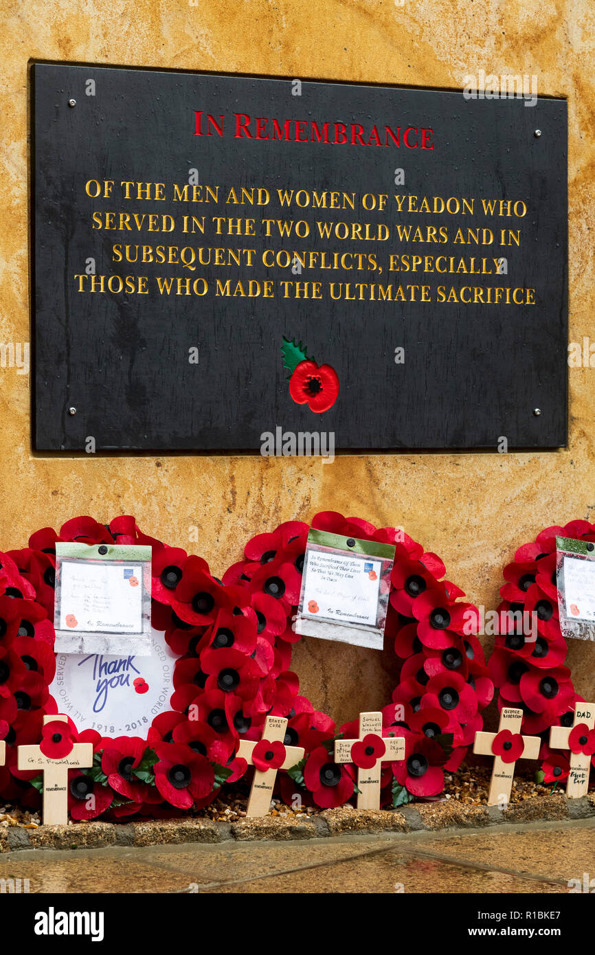 Yeadon, Leeds, West Yorkshire, UK 11th November, 2018. Close-up of the plaque inscription & crosses & poppy wreaths laid at the base of the new war memorial stone in front of Yeadon Methodist Church, on the anniversary of the end of the First World War. Ian Lamond/Alamy Live News Stock Photo