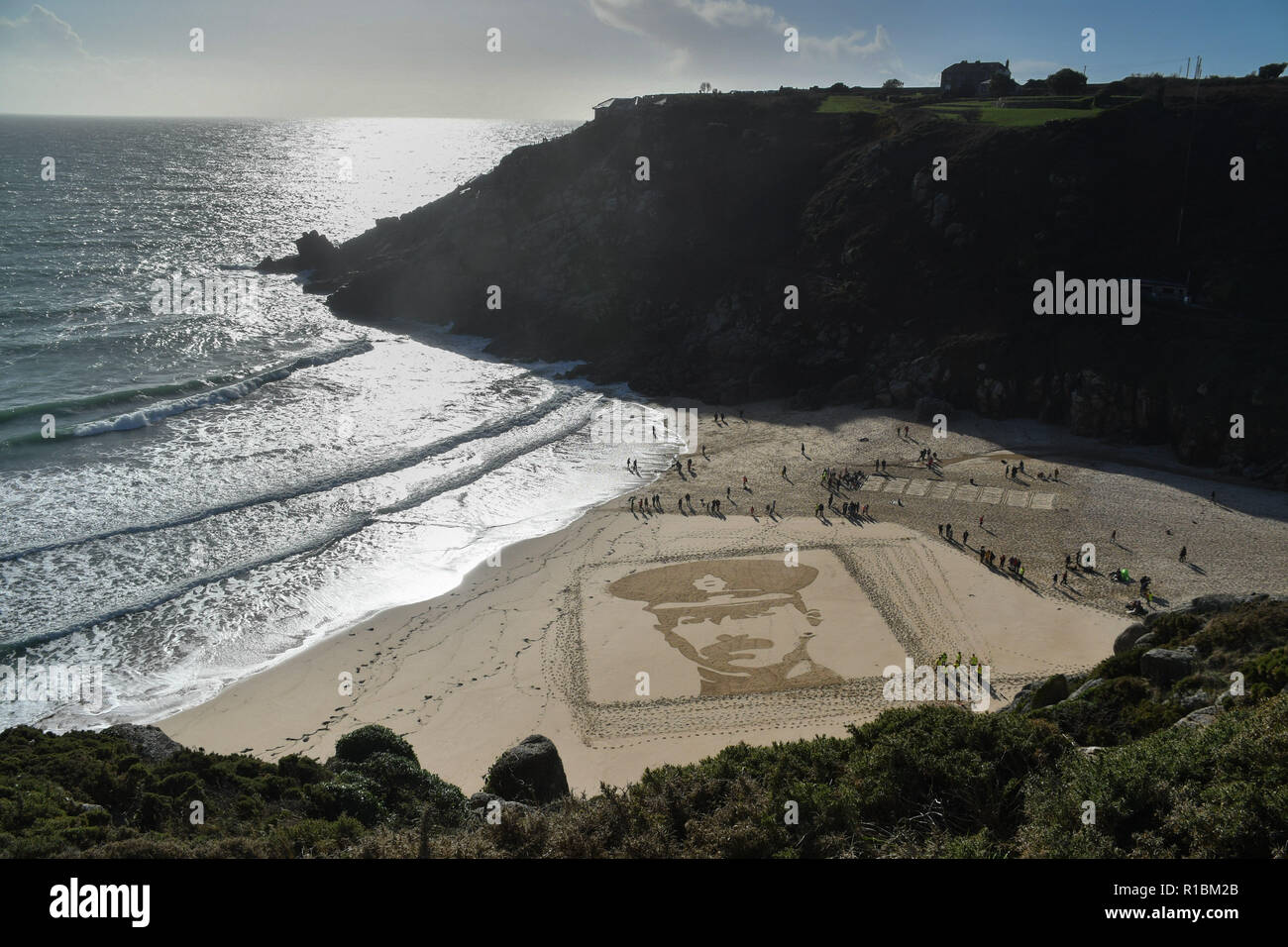 Porthcurno, Cornwall, UK. 11th Nov, 2018. A giant sand images was made on the beach at Porthcurno today. It was part of the 14-18 Now art commissions. This image depects RICHARD CHARLES GRAVES-SAWLE COLDSTREAM GUARDS AGE: 26 DATE OF DEATH: 02/11/1914 Son of Rear-Admiral Sir Charles Graves-Sawle, 4th Bart, and Lady Graves-Sawle, of 60, Queen's Gate, London; husband of Muriel Heaton-Ellis (now Mrs. A. L. C. Cavendish). Credit: Simon Maycock/Alamy Live News - Stock Image