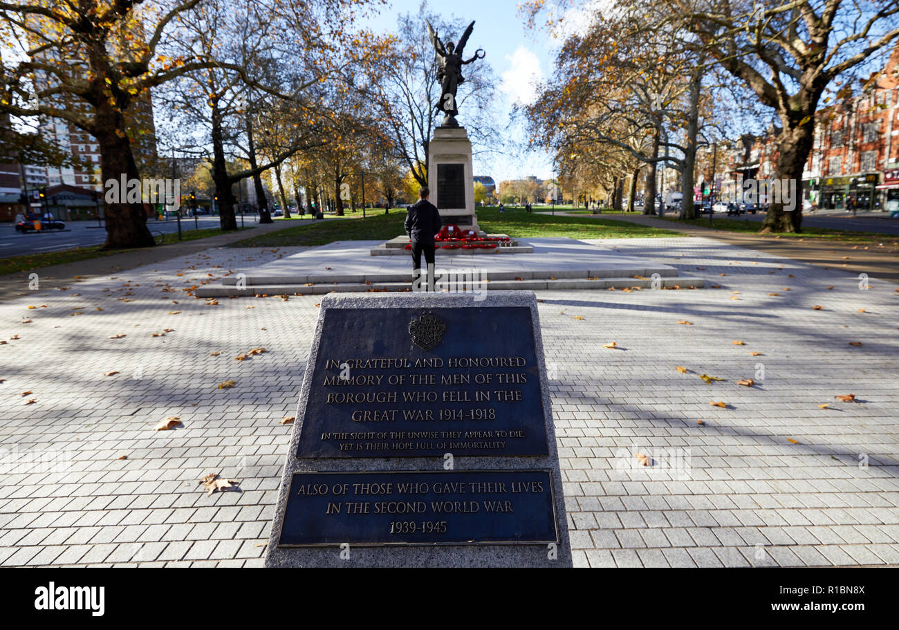 London, UK. - 11 November 2018: A man reflects at the Hammersmith War Memorial on Shepherd's Bush Green on the 100th anniversary since the end of World War One. Credit: Kevin J. Frost/Alamy Live News - Stock Image