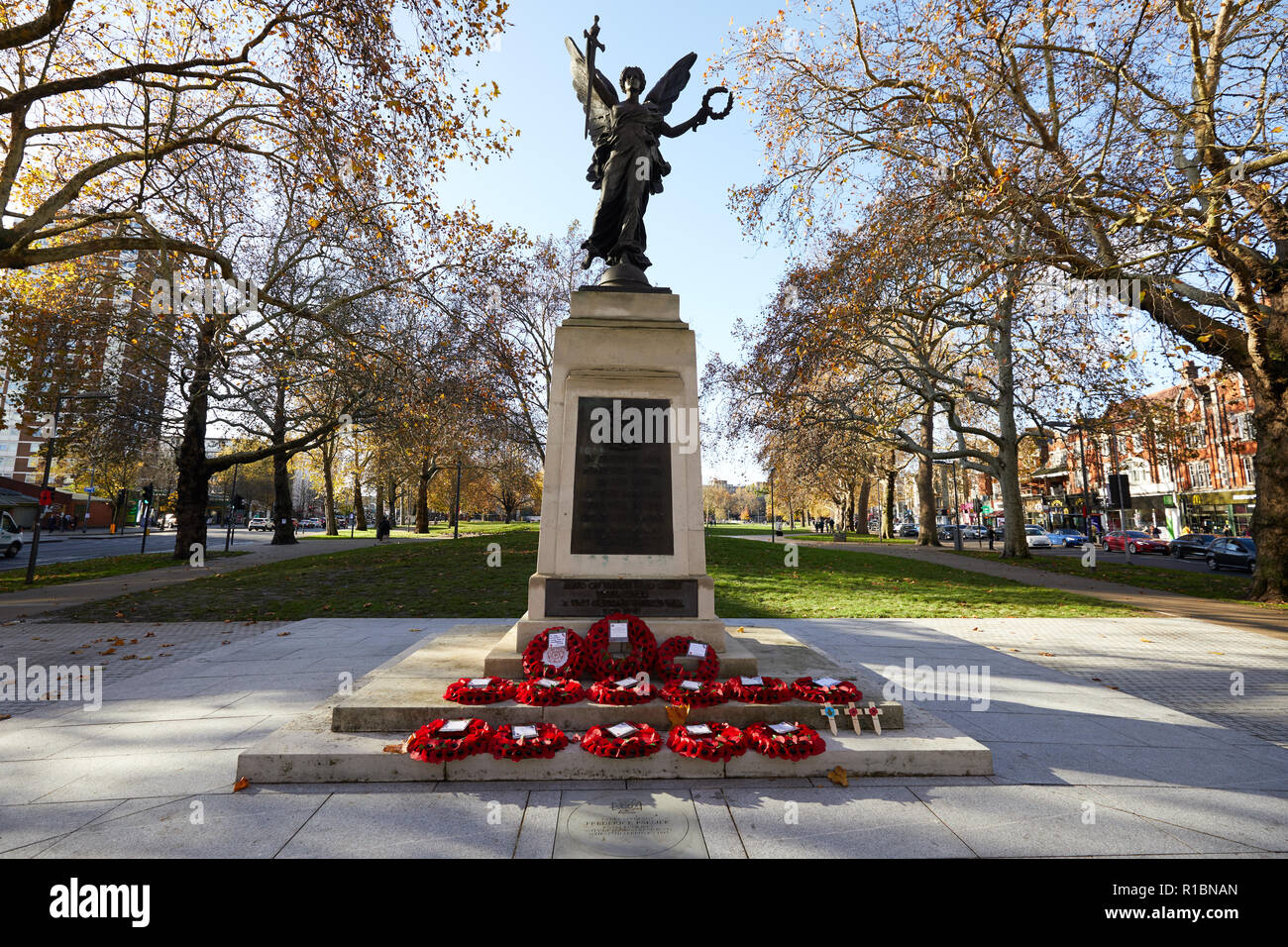 London, UK. - 11 November 2018: Poppy wreaths left at the Hammersmith War Memorial on Shepherd's Bush Green on the 100th anniversary since the end of World War One. Credit: Kevin J. Frost/Alamy Live News - Stock Image