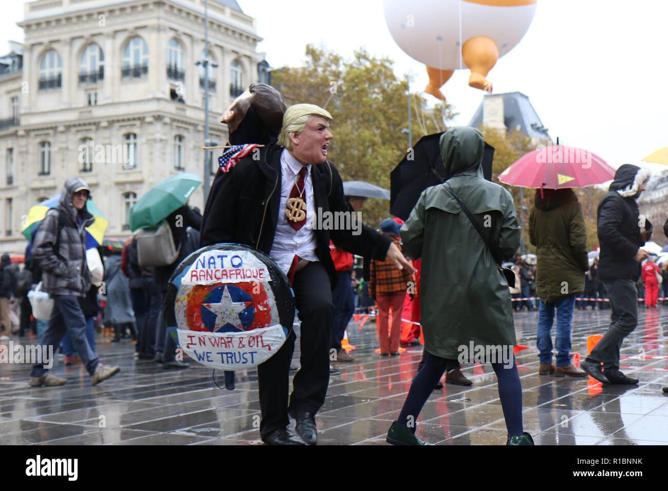 Paris, France. 11th Nov 2018.11 Nov 2018, Paris, France - A demonstrator in a Trump mask engages with others at Place de la République in Paris during an anti-Trump demonstration. Credit: Justin S. Johnson/Alamy Live News - Stock Image