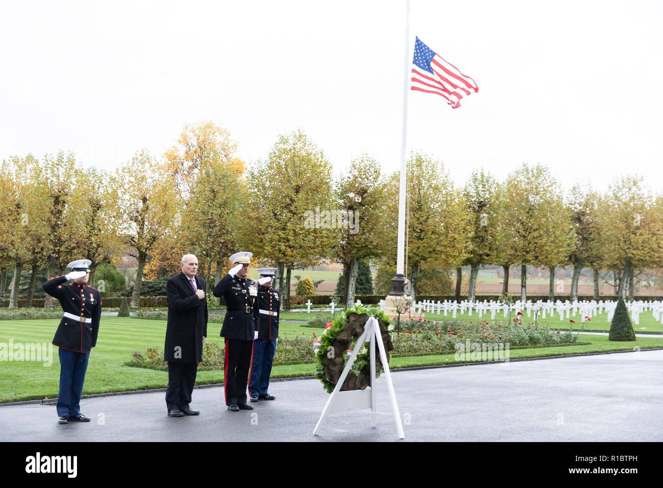 U.S Joint Chiefs Chairman Gen. Joseph Dunford, center, and White House Chief of Staff John Kelly, left, salute during a ceremony at the Aisne - Marne American Cemetery near the World War One battle ground of Belleau Wood November 10, 2018 in Belleau, France. President Donald Trump was scheduled to attend the ceremony but cancelled due to inclement weather. - Stock Image