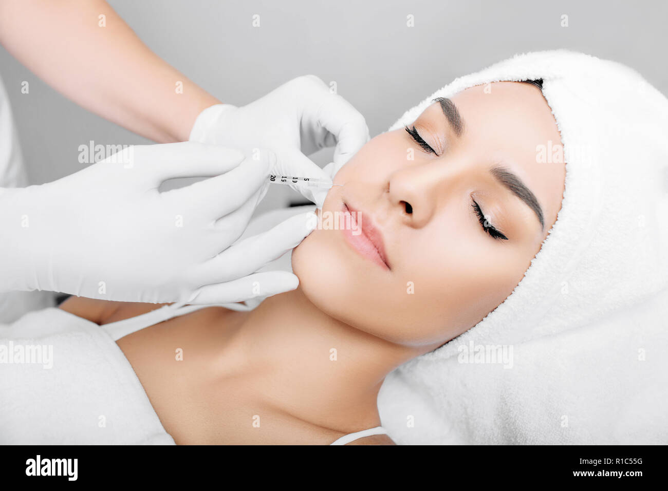 Beautiful woman having facial injection into area near mouth and nose. Anti age collagen injections into face. Beautician making injections for faceli - Stock Image