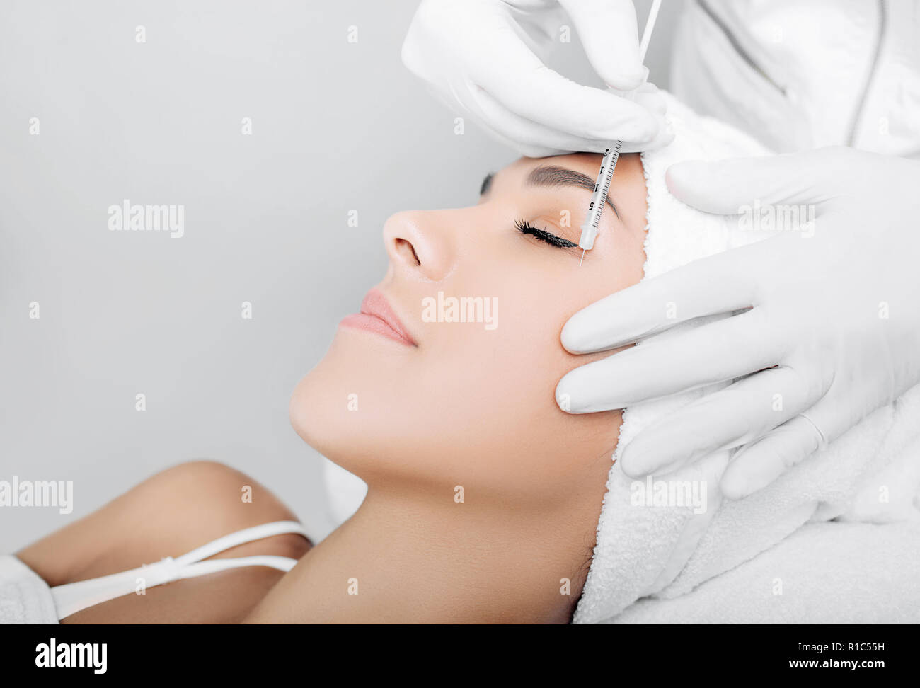 Beautiful woman having facial injection into area near eye. Anti age collagen injections into face. Beautician making injections against wrinkles arou - Stock Image