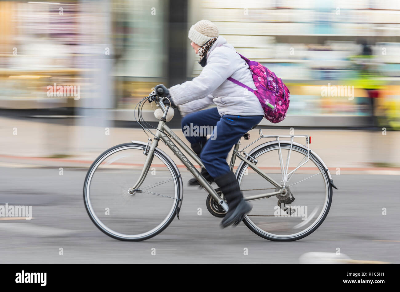 Side view of middle aged woman riding a Ridgeback bicycle wearing hat, coat & backpack, showing motion blur, UK. Female cycling. Female cyclist. - Stock Image