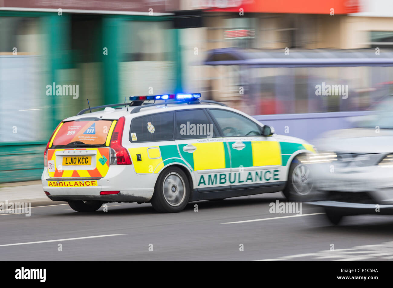 Ambulance fast response car with blue lights flashing on way to emergency call in West Sussex, UK. Motion blur effect. - Stock Image