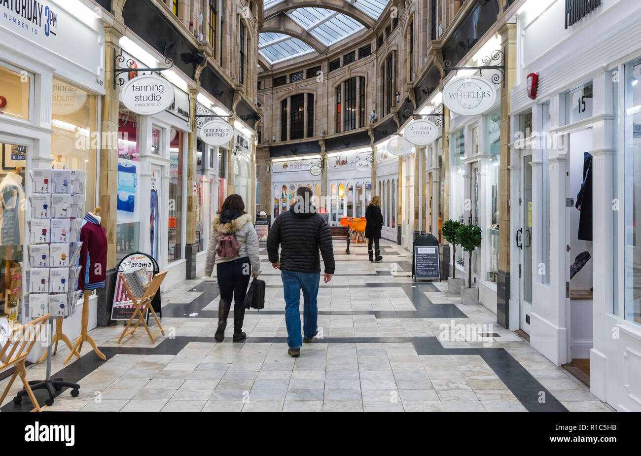 People walking through the Royal Arcade Shopping Centre, a small shopping mall in Worthing, West Sussex, England, UK. - Stock Image