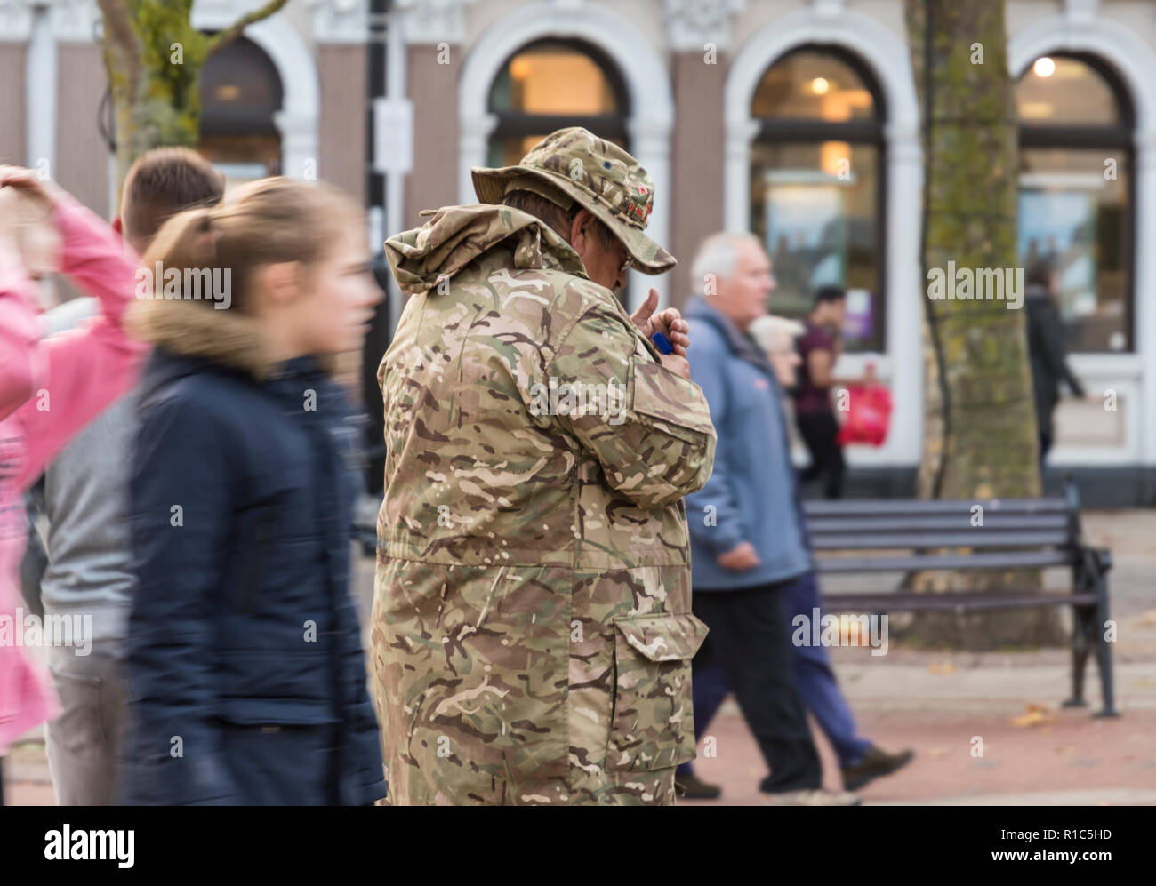 Middle aged man in military uniform on a busy public street lighting a cigarette, in the UK. Passive smoking. - Stock Image