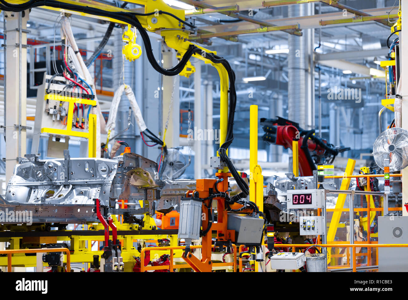 robot arm holds the detail of car. Car manufacturing plant - Stock Image