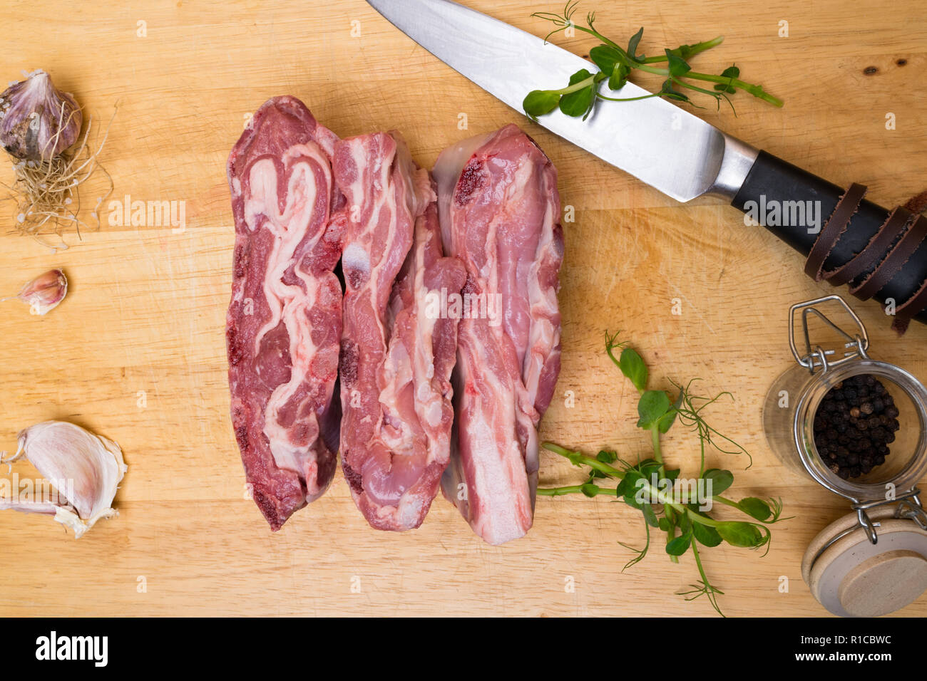 Raw fresh Lamb Meat with garlic, black pepper, greens and knife on wooden background - Stock Image