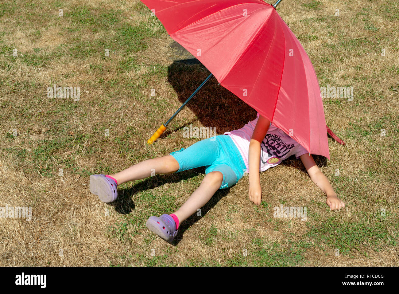 Young girl keeping out of the sun during the 2018 hot summer - Stock Image