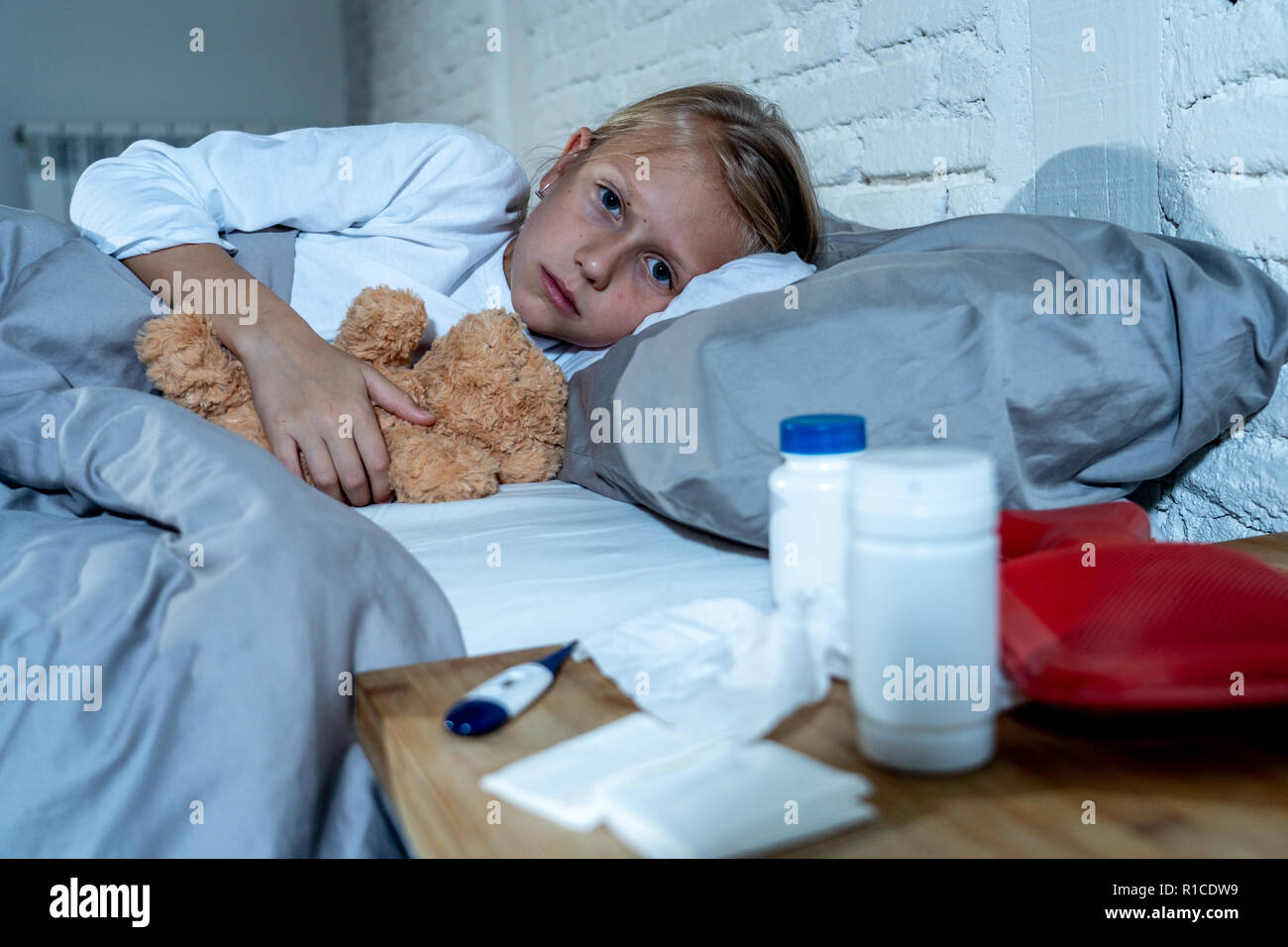 Sweet sick cute girl feeling sick lying in bed with medicines thermometer hot water bag suffering from Cold and Winter Flu Virus Sneezing Running Nose Stock Photo