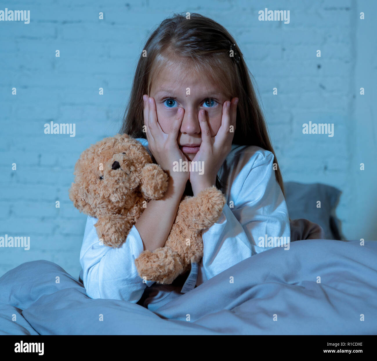 Scared little girl sitting in bed covering her face with hands holding her teddy in fear afraid of monsters in darkness in bedroom in Child nightmares - Stock Image