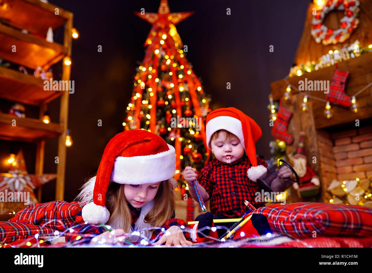 Charming girl in Santa hat lying on the floor and writes letter, draws with pencil and her little brother who interferes with her, plays with pencils in warm room with garlands, lights - Stock Image
