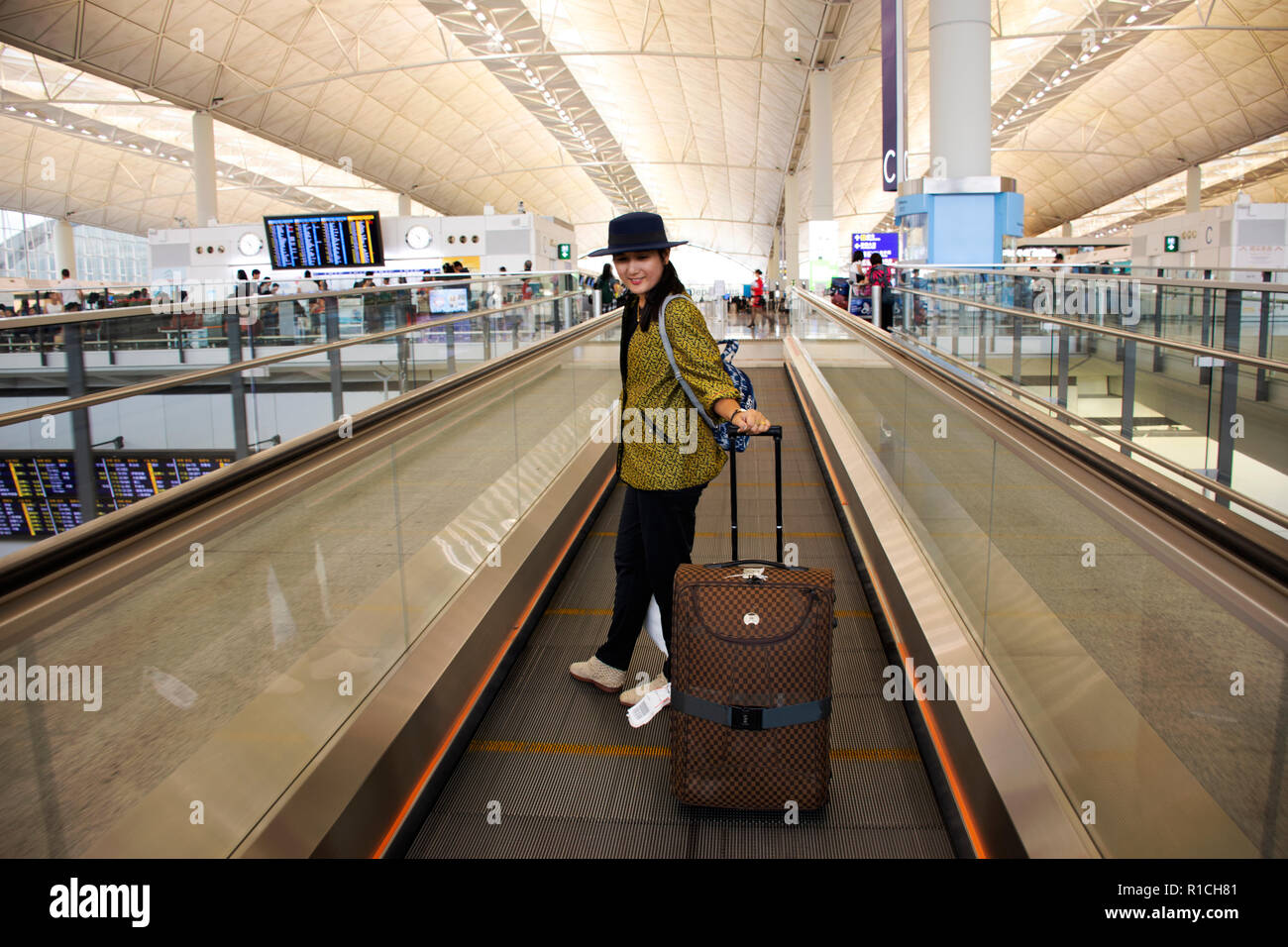 Travelers thai woman walking and drag luggage on escalator in terminal at Chek Lap Kok or Hong Kong International Airport on September 10, 2018 in Hon - Stock Image