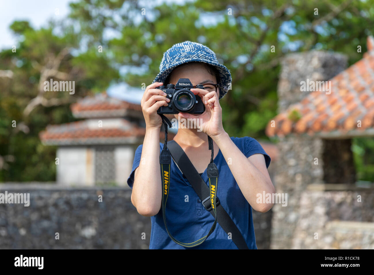 Japanese tourist taking a photo with a Nikon F3 camera; Mabuni Hill Observation Deck, Itoman, Okinawa, Japan - Stock Image