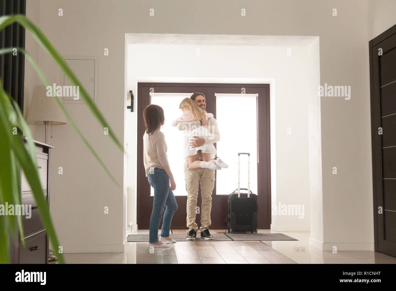 Happy family hugging in hallway at home - Stock Image