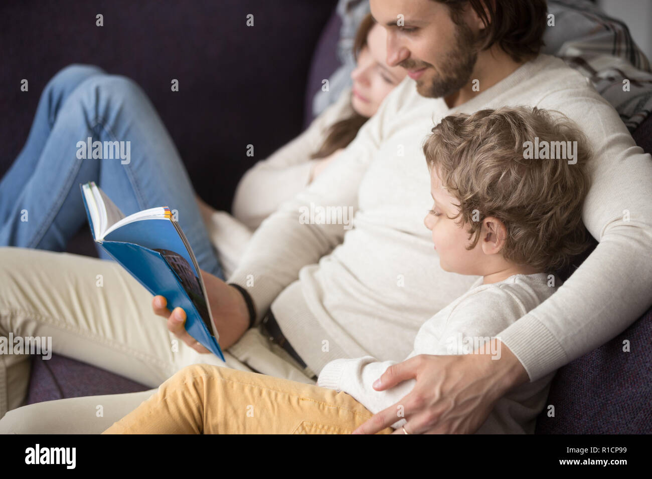 Family sitting on couch at home with a book - Stock Image