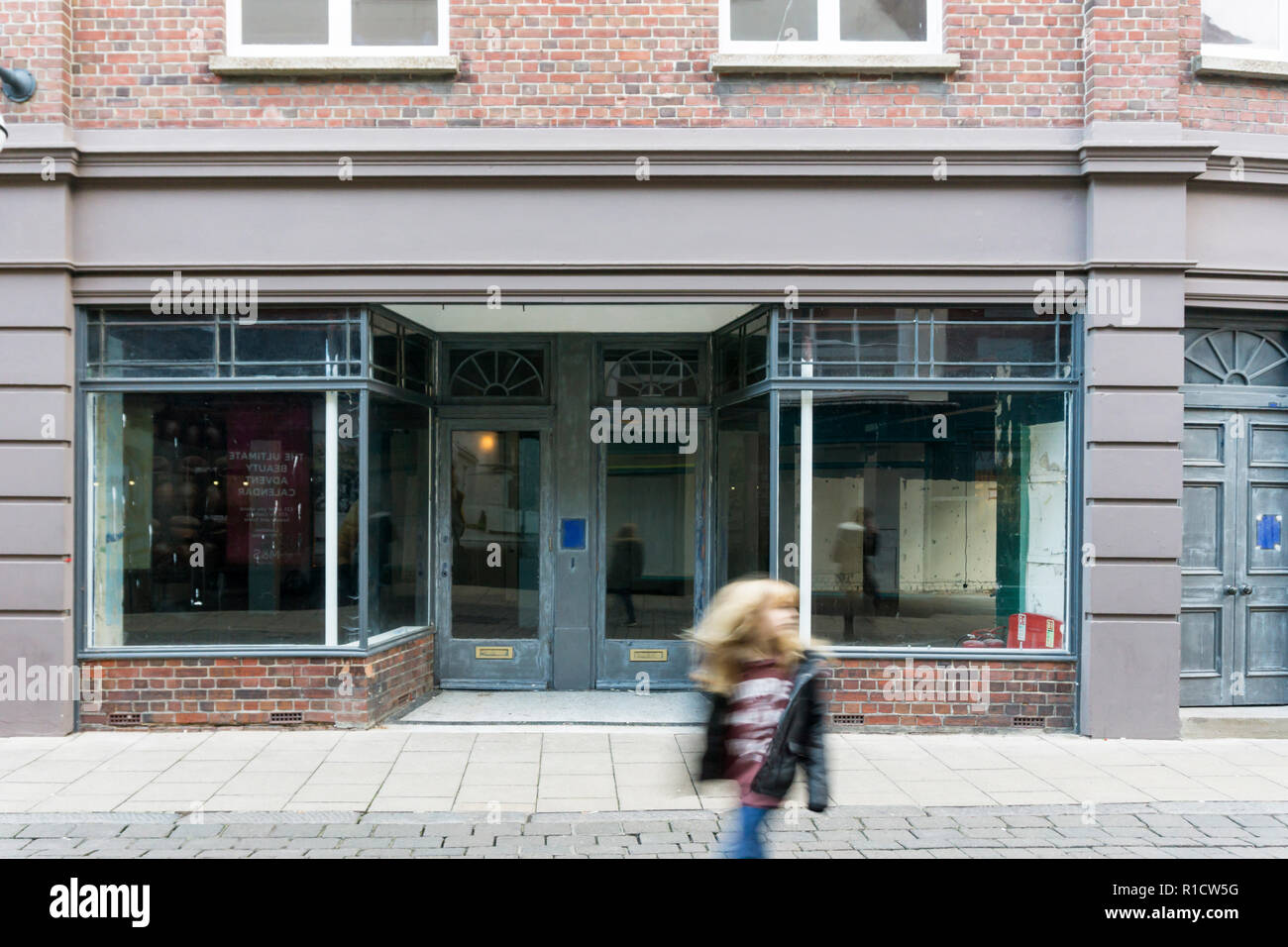 Girl, motion blurred, in front of an empty shop in a UK High Street. - Stock Image