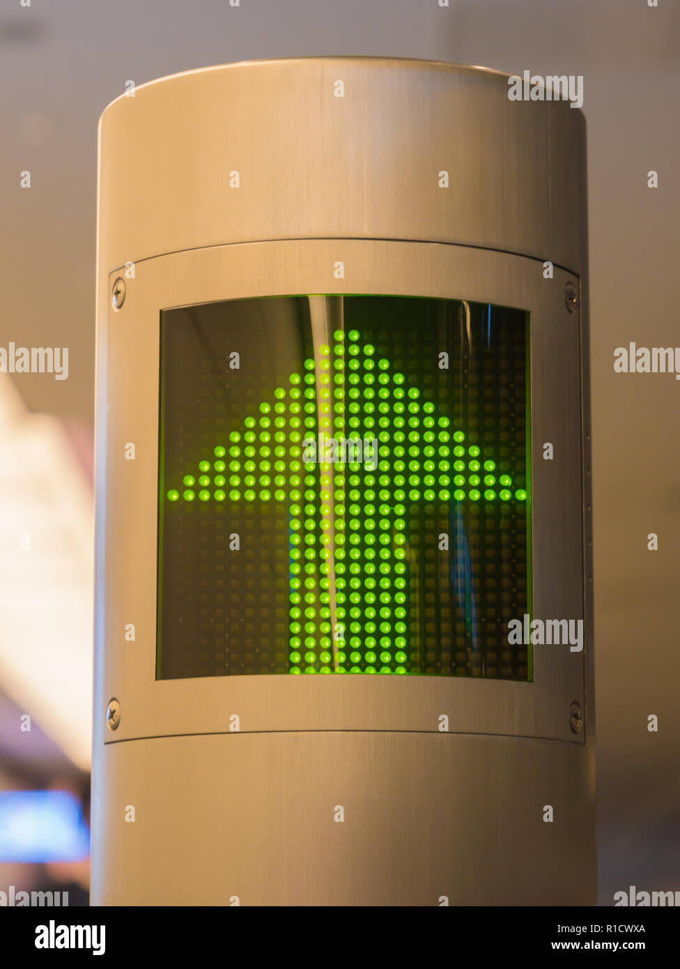 Illuminated green arrow sign that directs to the passage which leads to the departure gate - Stock Image