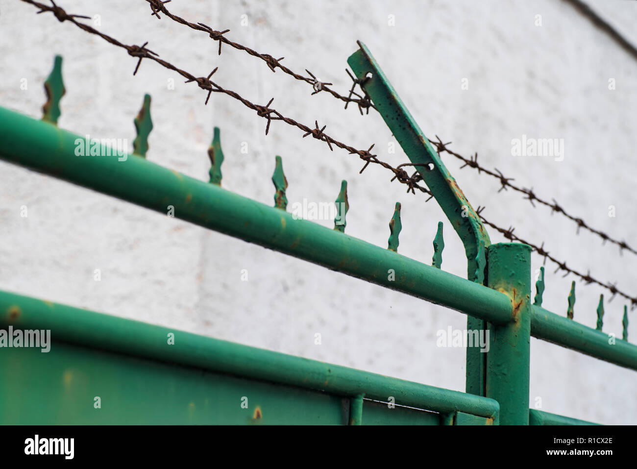 Metal fence with barbed wire, guarded object. Barbed wire on the fence. - Stock Image