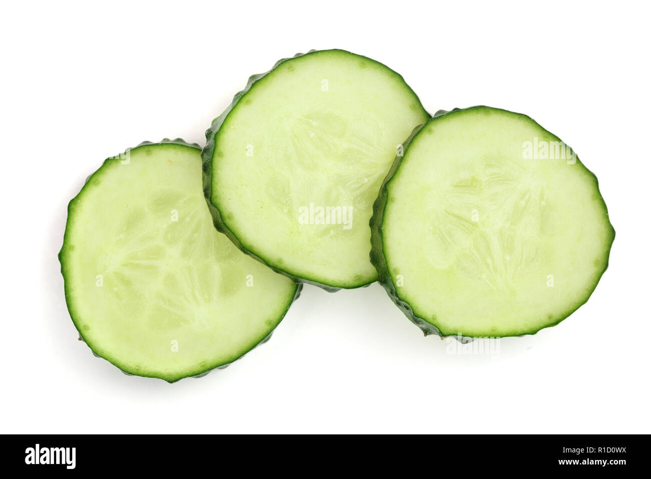 Cucumber slices isolated on white background. Top view. Flat lay pattern - Stock Image