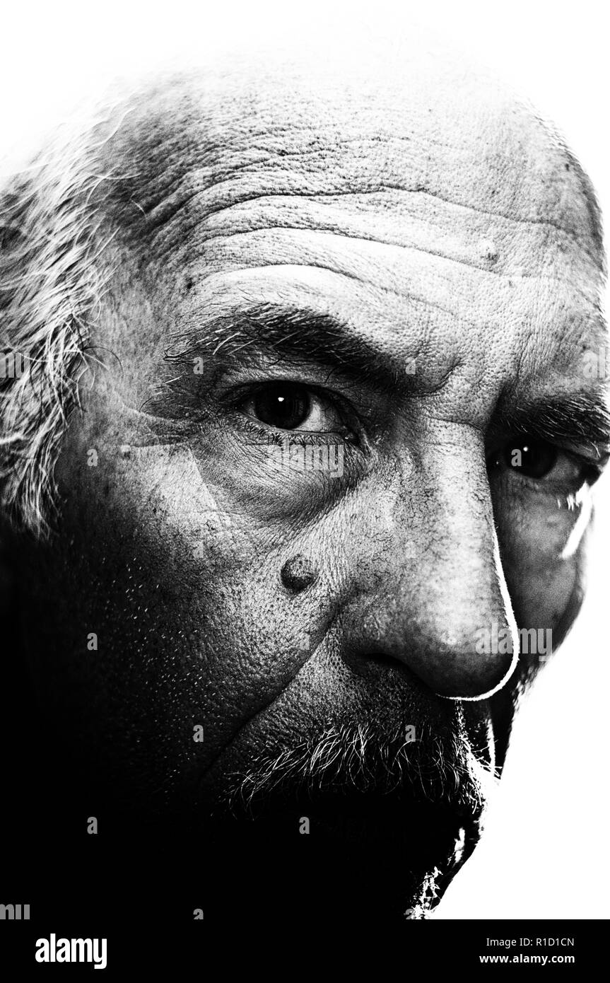 Highly detailed, high contrast, close up, black and white portrait of man with head turned looking at viewer. Visible grain at 100% - Stock Image