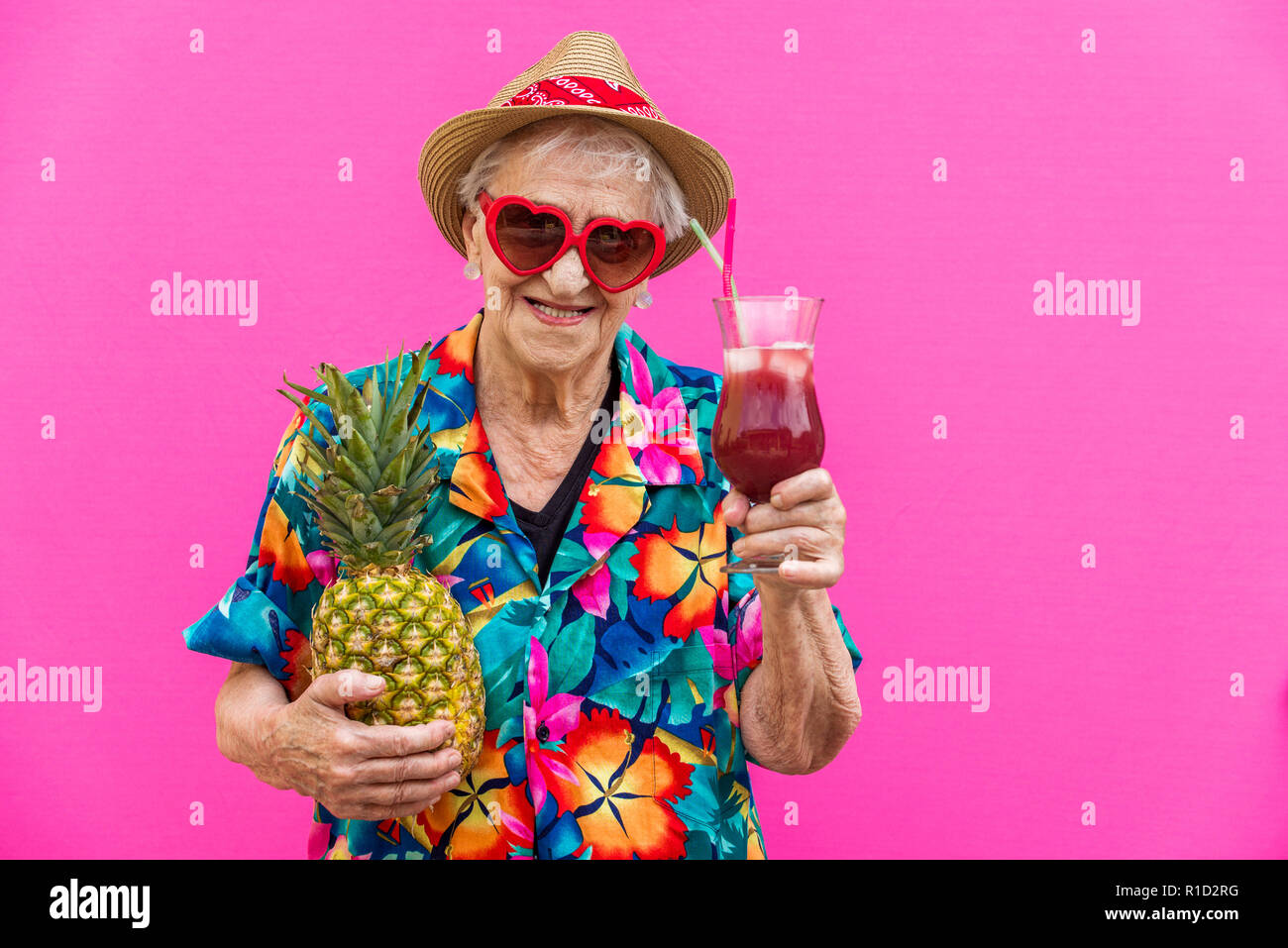 Funny and extravagant senior woman posing on colored background - Youthful old woman in the sixties having fun and partying - Stock Image