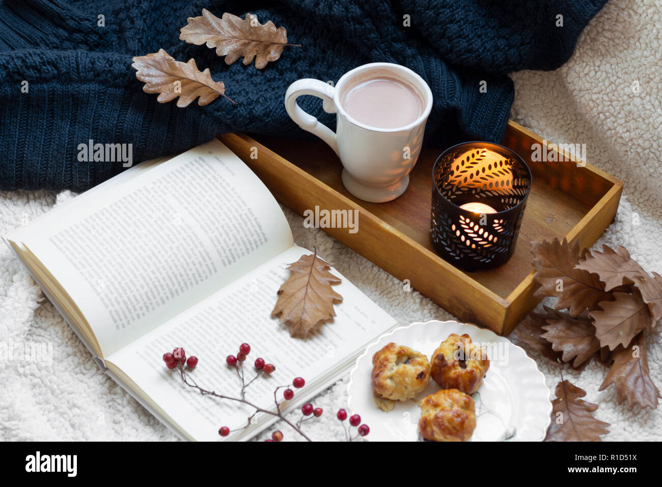 Hygge style. book and mug of coffee wrapped in warm scarf. - Stock Image