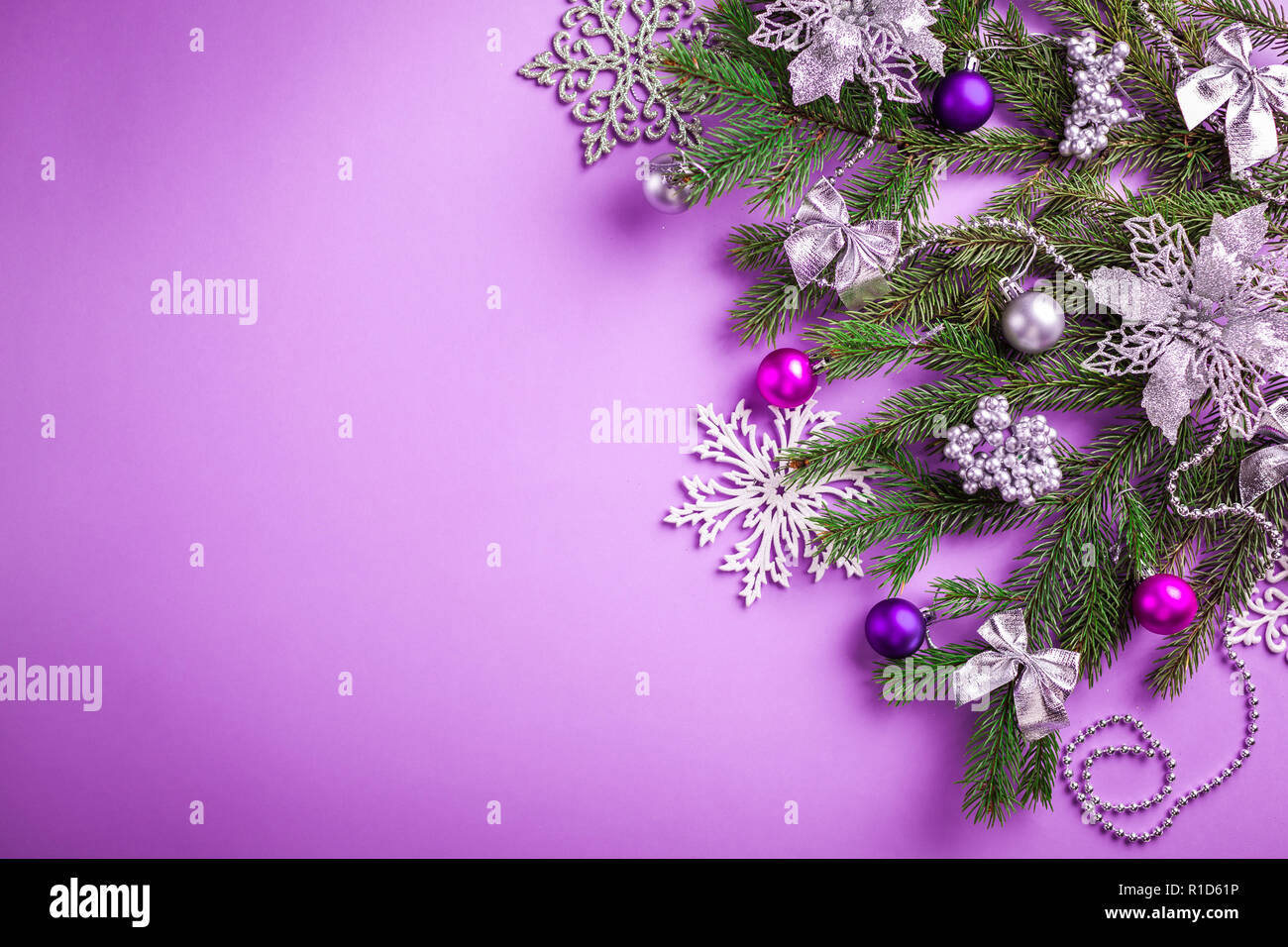 purple christmas and new year background with decorated fir tree and toys copy space