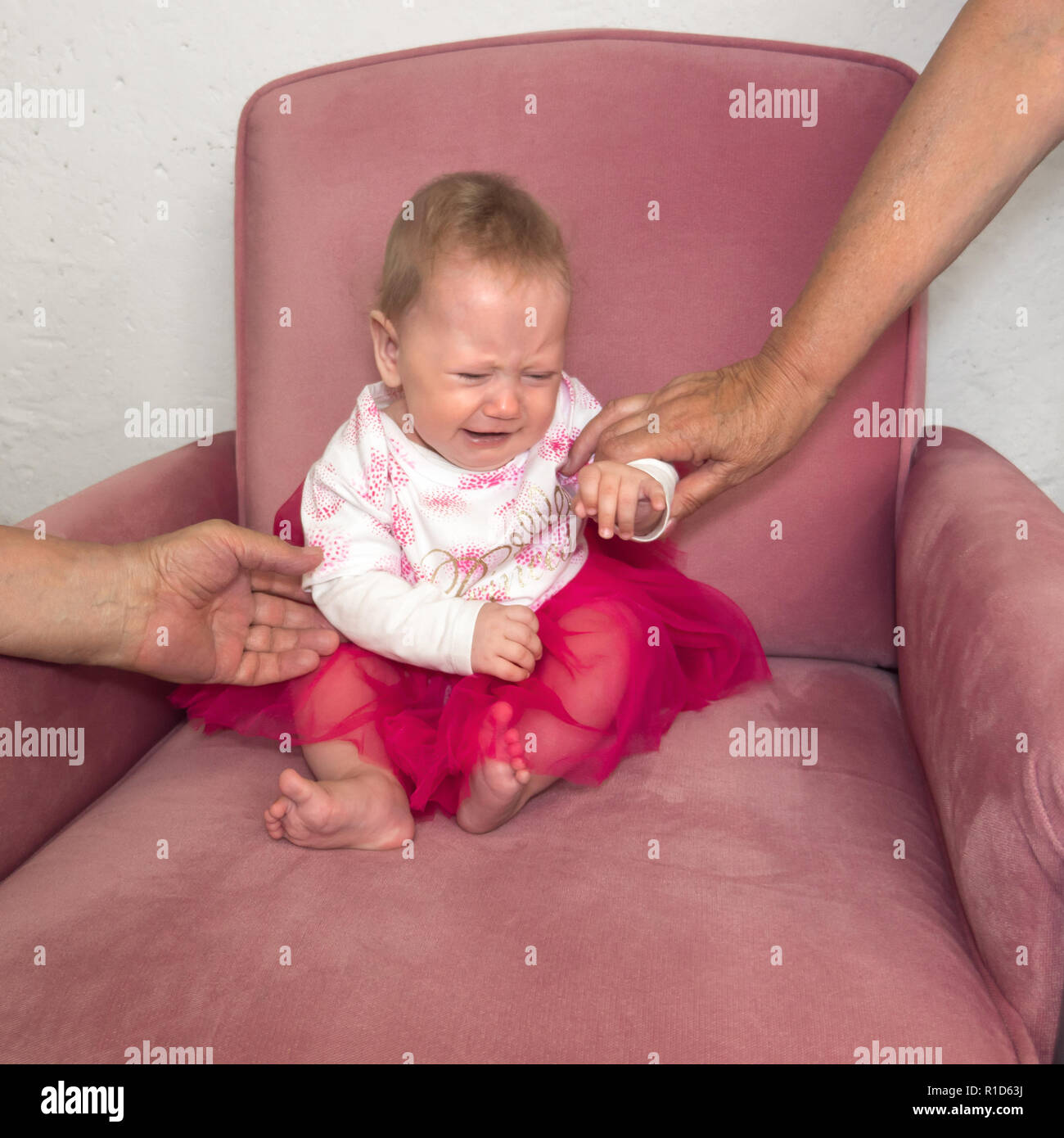 Crying baby sitting in the chair. Hands of grandmother holding child sitting in the chair. Negative child emotion. Facial expression. Portrait of dressed up girl sitting in the chair. - Stock Image