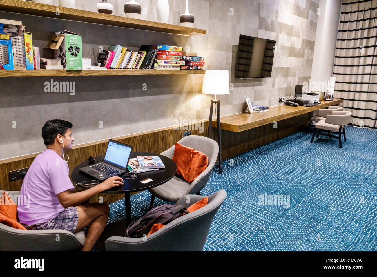 London England United Kingdom Great Britain Lambeth Staybridge Suites London Vauxhall hotel inside interior business center lobby play area Asian man - Stock Image
