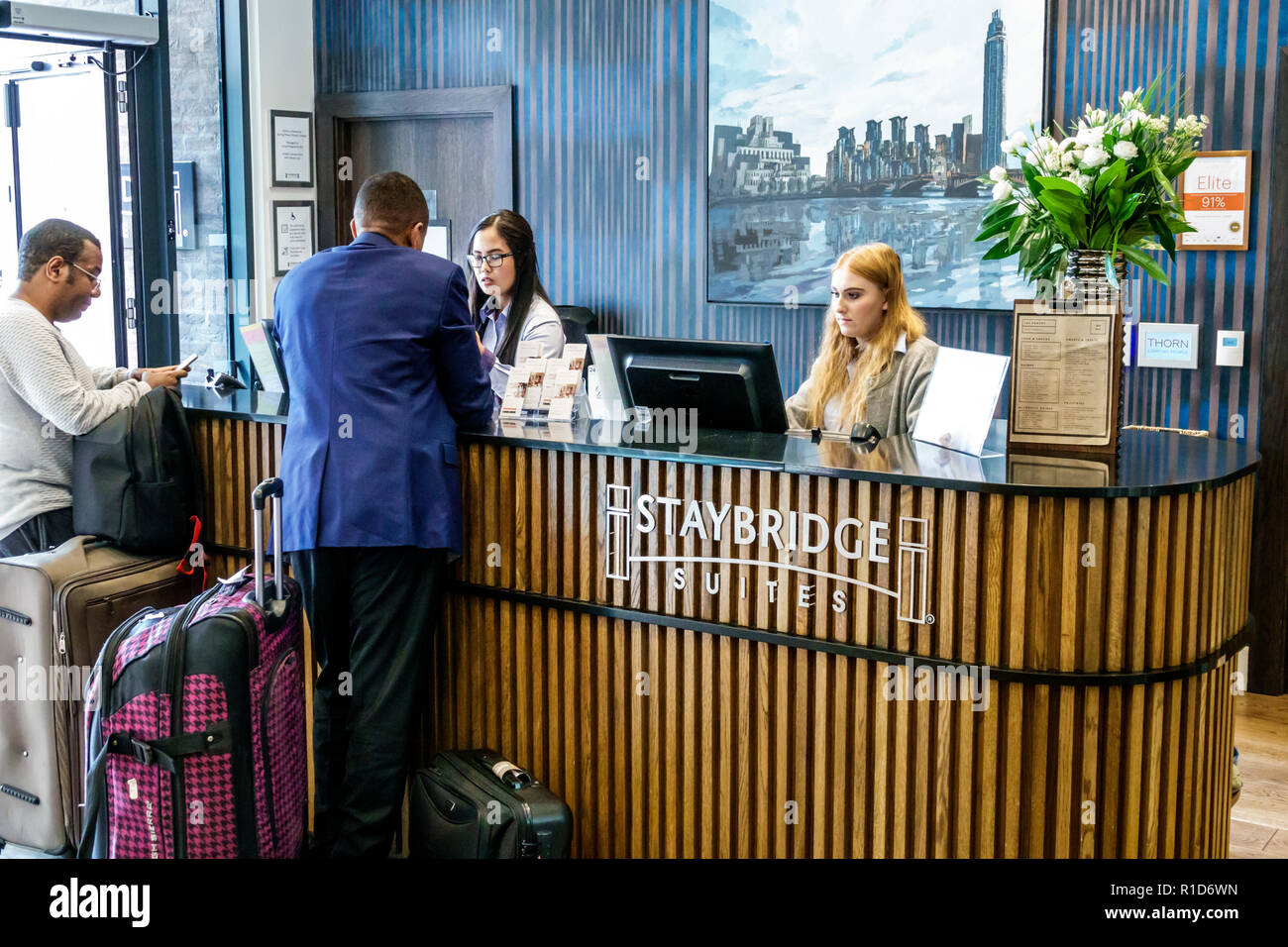 London England United Kingdom Great Britain Lambeth Staybridge Suites London Vauxhall hotel inside interior front desk clerk employee check-in clerk g - Stock Image