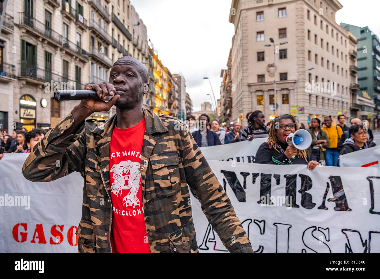 A black man is seen singing slogans with a microphone during the demonstration. A new manifestation against institutional racism has crossed the streets of the center of Barcelona. Accompanied by social organizations and the Trade Union of street vendors, more than 500 people have claimed to end racism in Barcelona and have denounced police identifications according to the color of their skin. - Stock Image