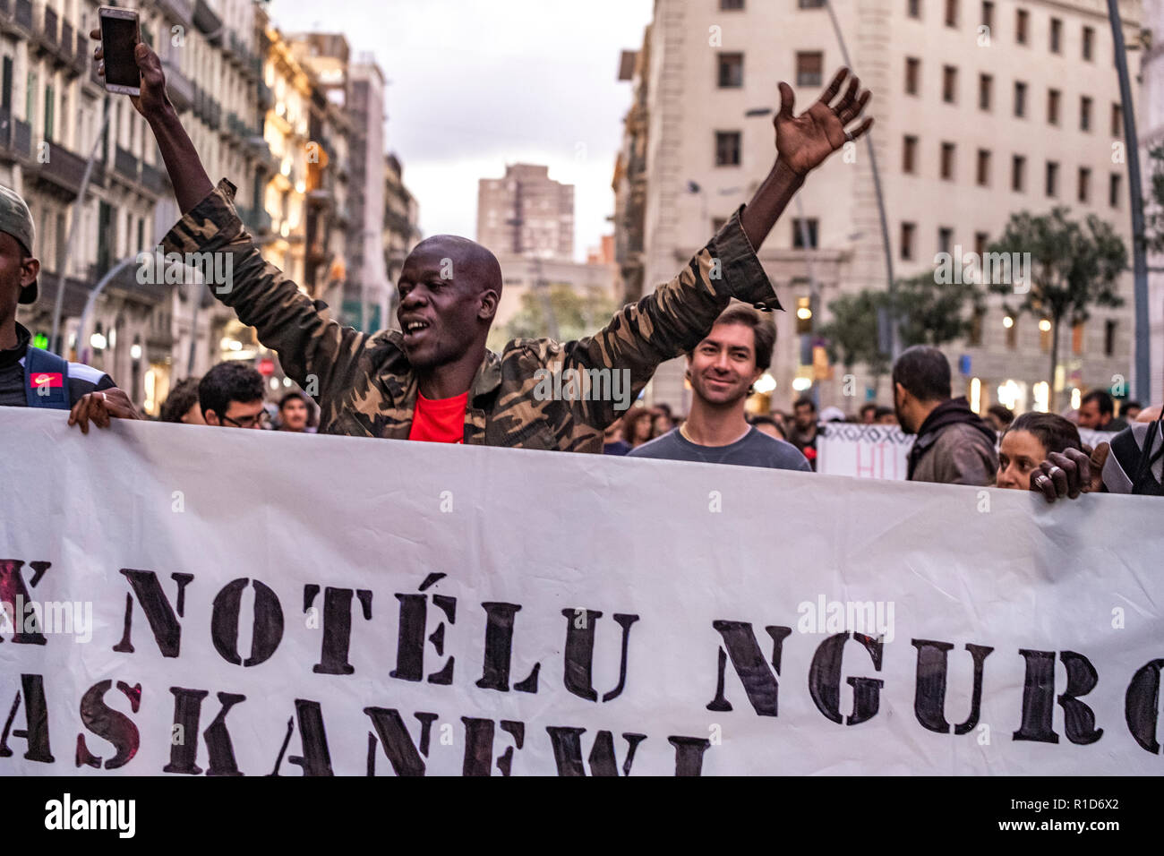 A black man is seen raising his hands during the demonstration. A new manifestation against institutional racism has crossed the streets of the center of Barcelona. Accompanied by social organizations and the Trade Union of street vendors, more than 500 people have claimed to end racism in Barcelona and have denounced police identifications according to the color of their skin. - Stock Image