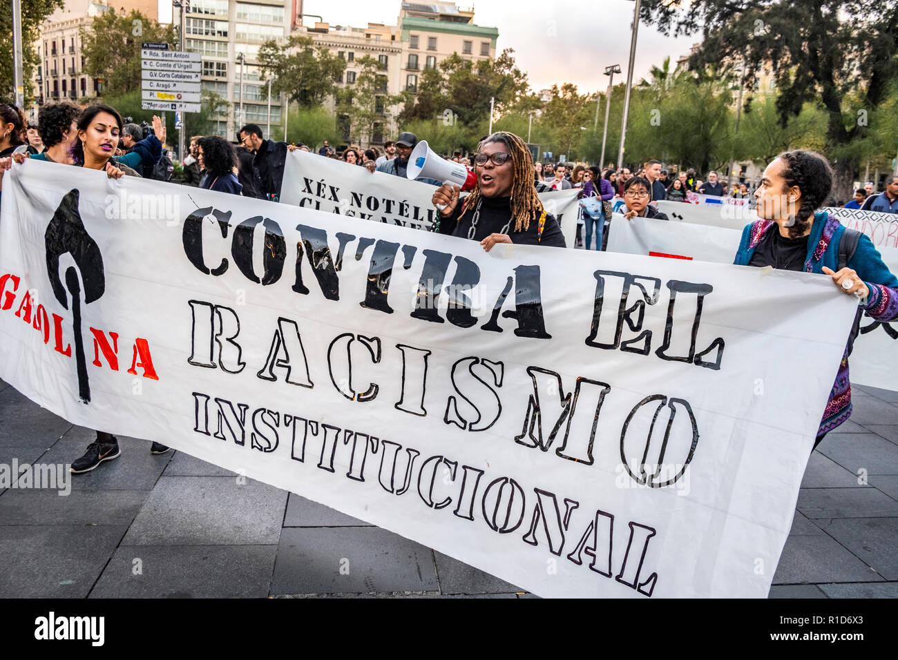 A woman with a megaphone is seen behind a banner during the demonstration. A new manifestation against institutional racism has crossed the streets of the center of Barcelona. Accompanied by social organizations and the Trade Union of street vendors, more than 500 people have claimed to end racism in Barcelona and have denounced police identifications according to the color of their skin. - Stock Image
