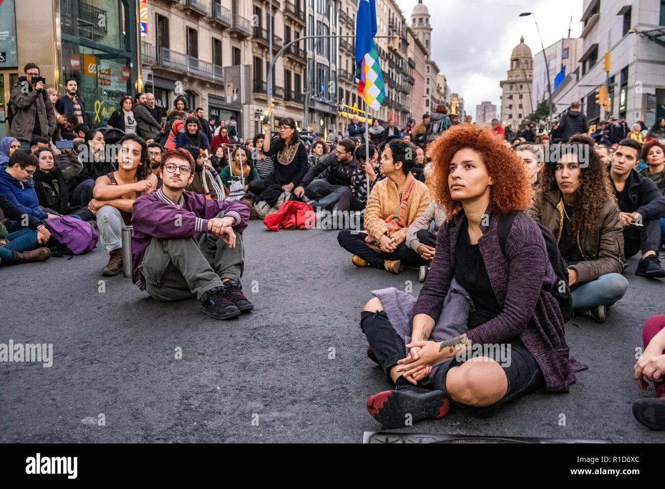 Several demonstrators are seen during the demonstration sitting listening to the statements. A new manifestation against institutional racism has crossed the streets of the center of Barcelona. Accompanied by social organizations and the Trade Union of street vendors, more than 500 people have claimed to end racism in Barcelona and have denounced police identifications according to the color of their skin. - Stock Image