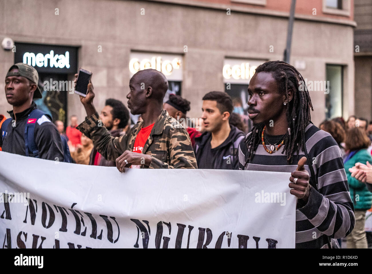 Several black protesters are seen behind the banner during the demonstration. A new manifestation against institutional racism has crossed the streets of the center of Barcelona. Accompanied by social organizations and the Trade Union of street vendors, more than 500 people have claimed to end racism in Barcelona and have denounced police identifications according to the color of their skin. - Stock Image