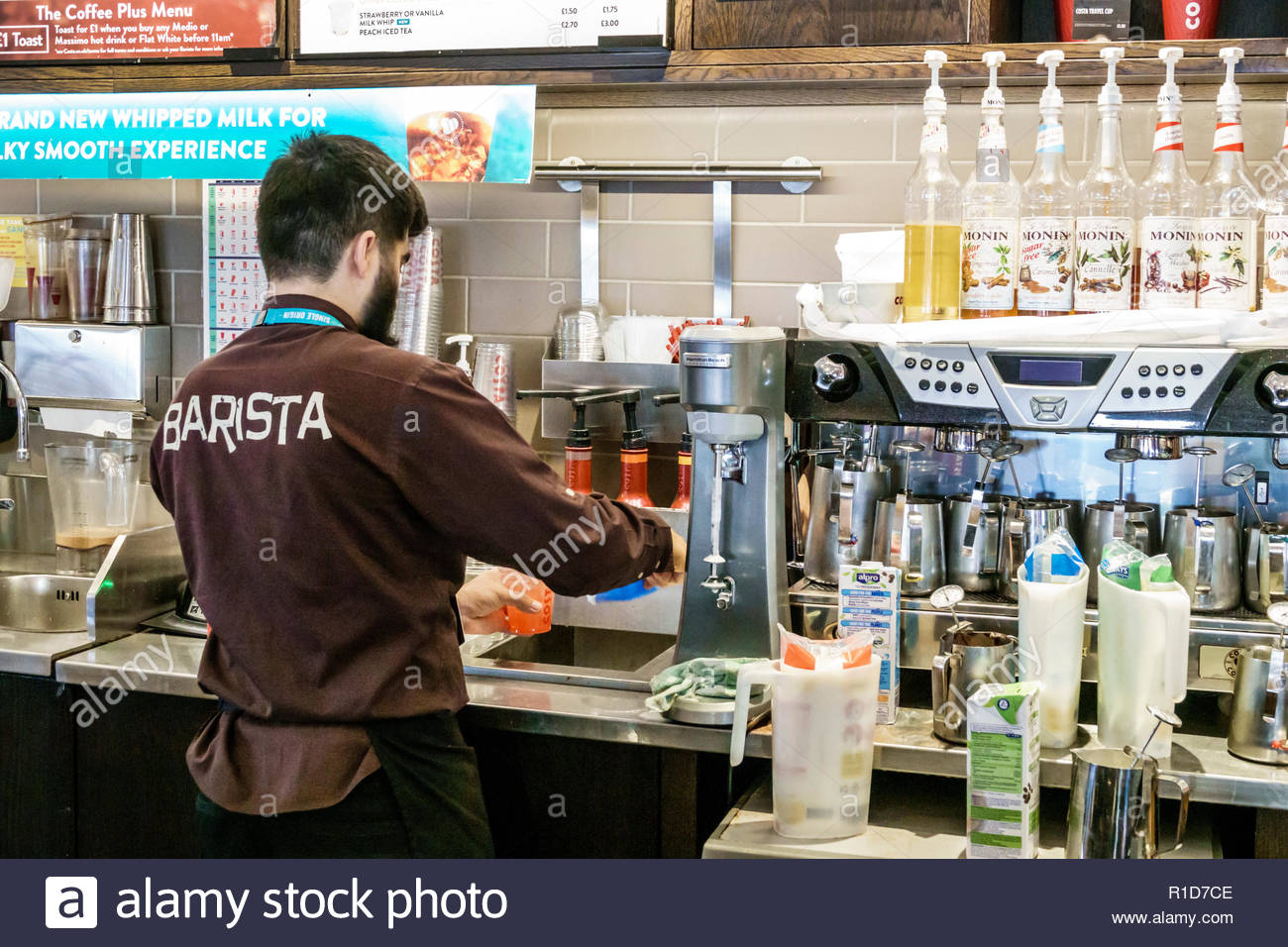 London England United Kingdom Great Britain Lambeth South Bank Costa Coffee cafe coffeehouse barista espresso machine making beverage man counter atte - Stock Image