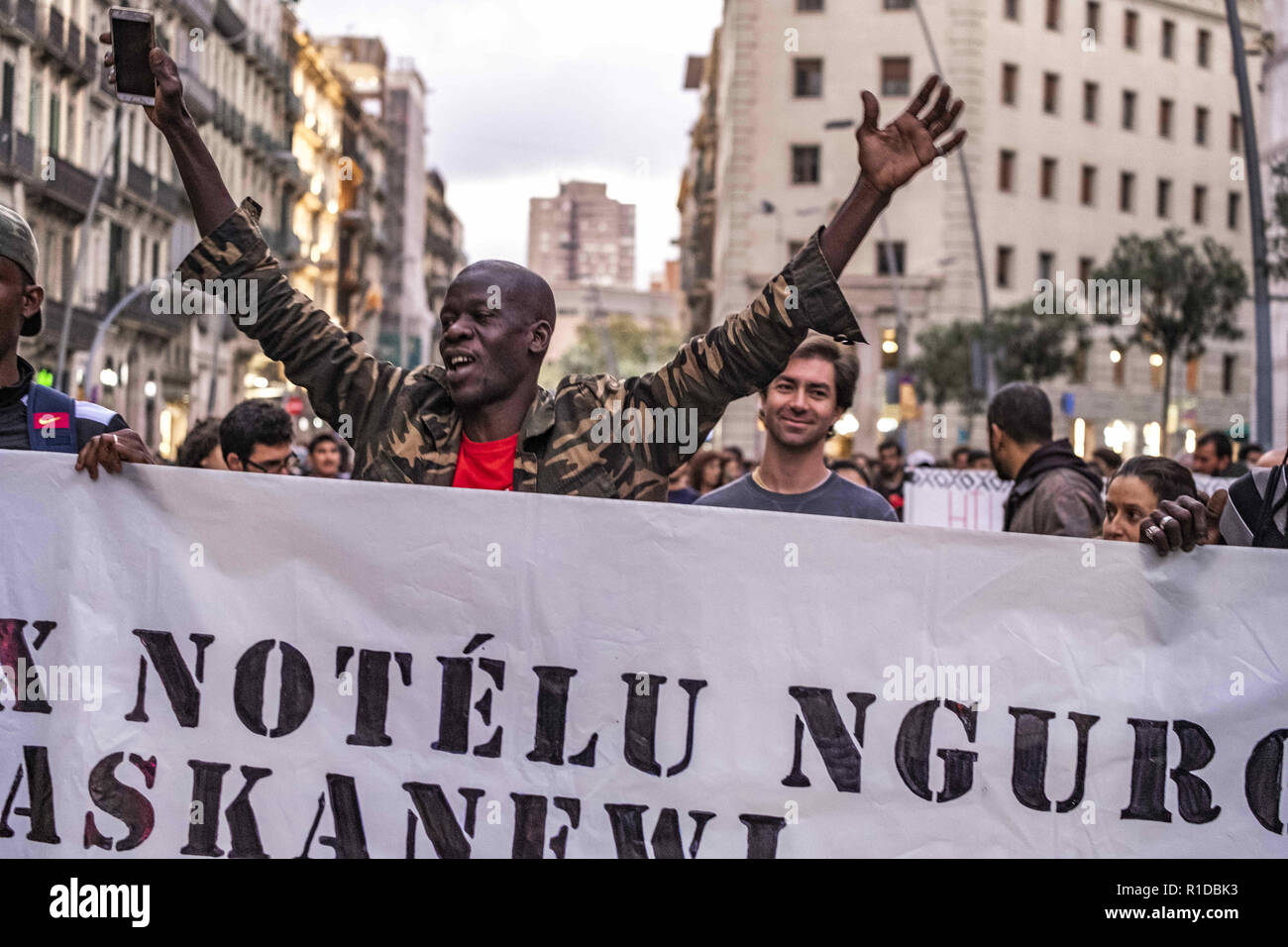 Barcelona, Catalonia, Spain. 11th Nov, 2018. A black man is seen raising his hands during the demonstration.A new manifestation against institutional racism has crossed the streets of the center of Barcelona. Accompanied by social organizations and the Trade Union of street vendors, more than 500 people have claimed to end racism in Barcelona and have denounced police identifications according to the color of their skin. Credit: Paco Freire/SOPA Images/ZUMA Wire/Alamy Live News - Stock Image