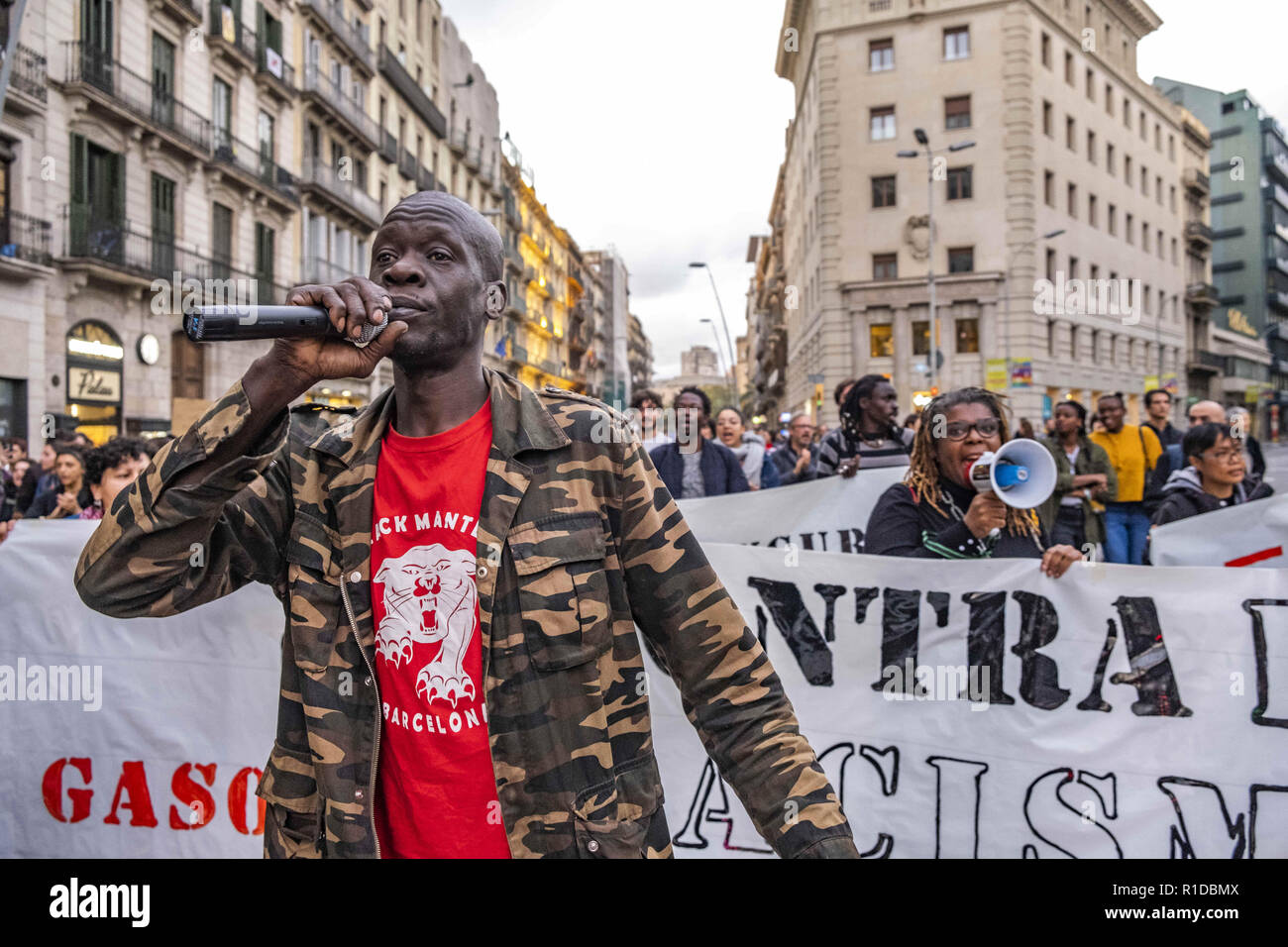 Barcelona, Catalonia, Spain. 11th Nov, 2018. A black man is seen singing slogans with a microphone during the demonstration.A new manifestation against institutional racism has crossed the streets of the center of Barcelona. Accompanied by social organizations and the Trade Union of street vendors, more than 500 people have claimed to end racism in Barcelona and have denounced police identifications according to the color of their skin. Credit: Paco Freire/SOPA Images/ZUMA Wire/Alamy Live News - Stock Image