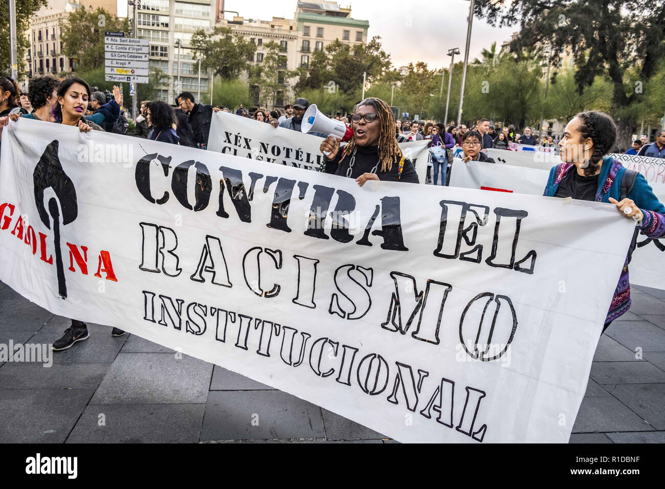 Barcelona, Catalonia, Spain. 11th Nov, 2018. A woman with a megaphone is seen behind a banner during the demonstration.A new manifestation against institutional racism has crossed the streets of the center of Barcelona. Accompanied by social organizations and the Trade Union of street vendors, more than 500 people have claimed to end racism in Barcelona and have denounced police identifications according to the color of their skin. Credit: Paco Freire/SOPA Images/ZUMA Wire/Alamy Live News - Stock Image