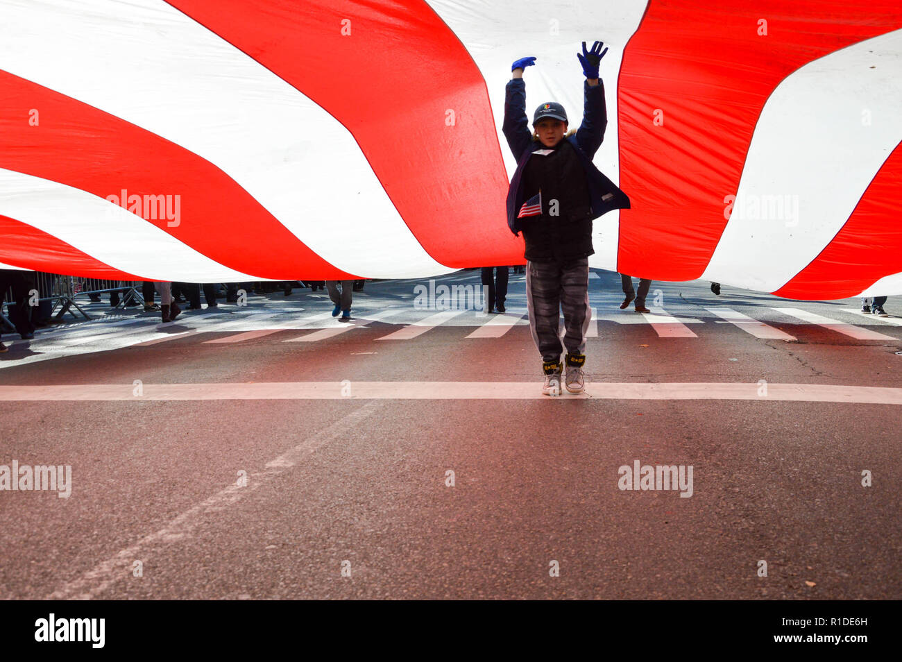Manhattan, New York, USA. 11th Nov, 2018. A kid seen under a huge flag during the parade. Thousands from more than 300 units in the Armed Forces took part in the Annual Veterans Day Parade. The Veterans Day Parade took place along the 5th Avenue in New York City honoring the service of those who've served in the U.S. Armed Forces. Credit: Ryan Rahman/SOPA Images/ZUMA Wire/Alamy Live News - Stock Image