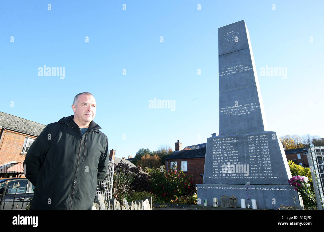 Londonderry, UK. 08th Nov, 2018. Gleann Doherty stands next to a memorial commemorating the victims of Bloody Sunday in 1972, when British soldiers shot 13 demonstrators and injured 13 others. Glenn's father Patrick Doherty was one of those killed on Bloody Sunday. Some of the worst acts of violence during the riots took place in the area. Today Derry is a tourist attraction because of the political murals. Credit: Jonathan Porter/PressEye/dpa/Alamy Live News - Stock Image
