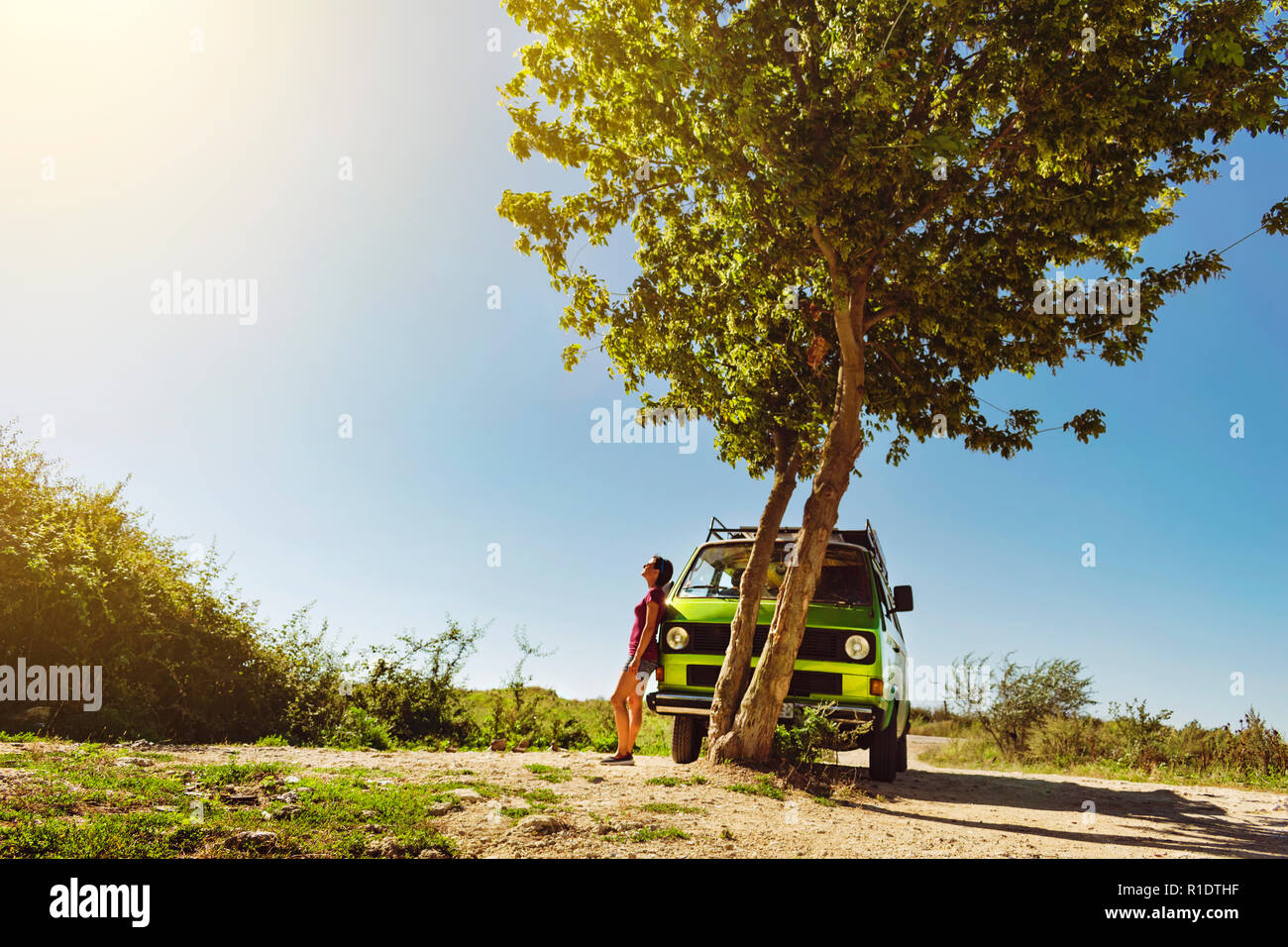Beautiful young girl in shorts standing beside old timer classic camper van beneath the tree on a bright and warm summer day Stock Photo